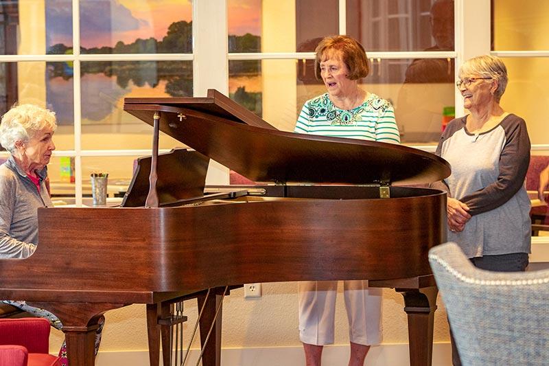 Seniors gathered around a baby grand piano