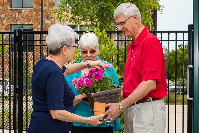 Three seniors admiring flowers, carrying gardening supplies