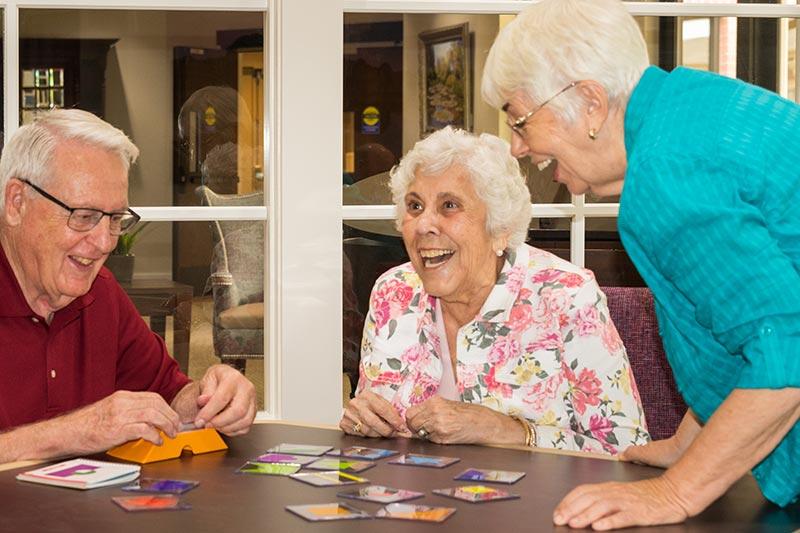 Three seniors playing a card game