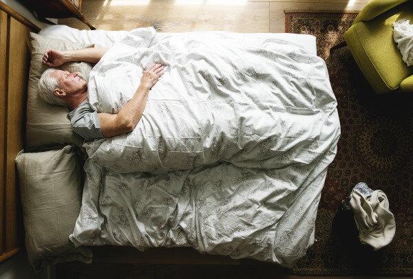 elderly-caucasian-man-sleeping-on-the-bed-phj9vkk.jpg