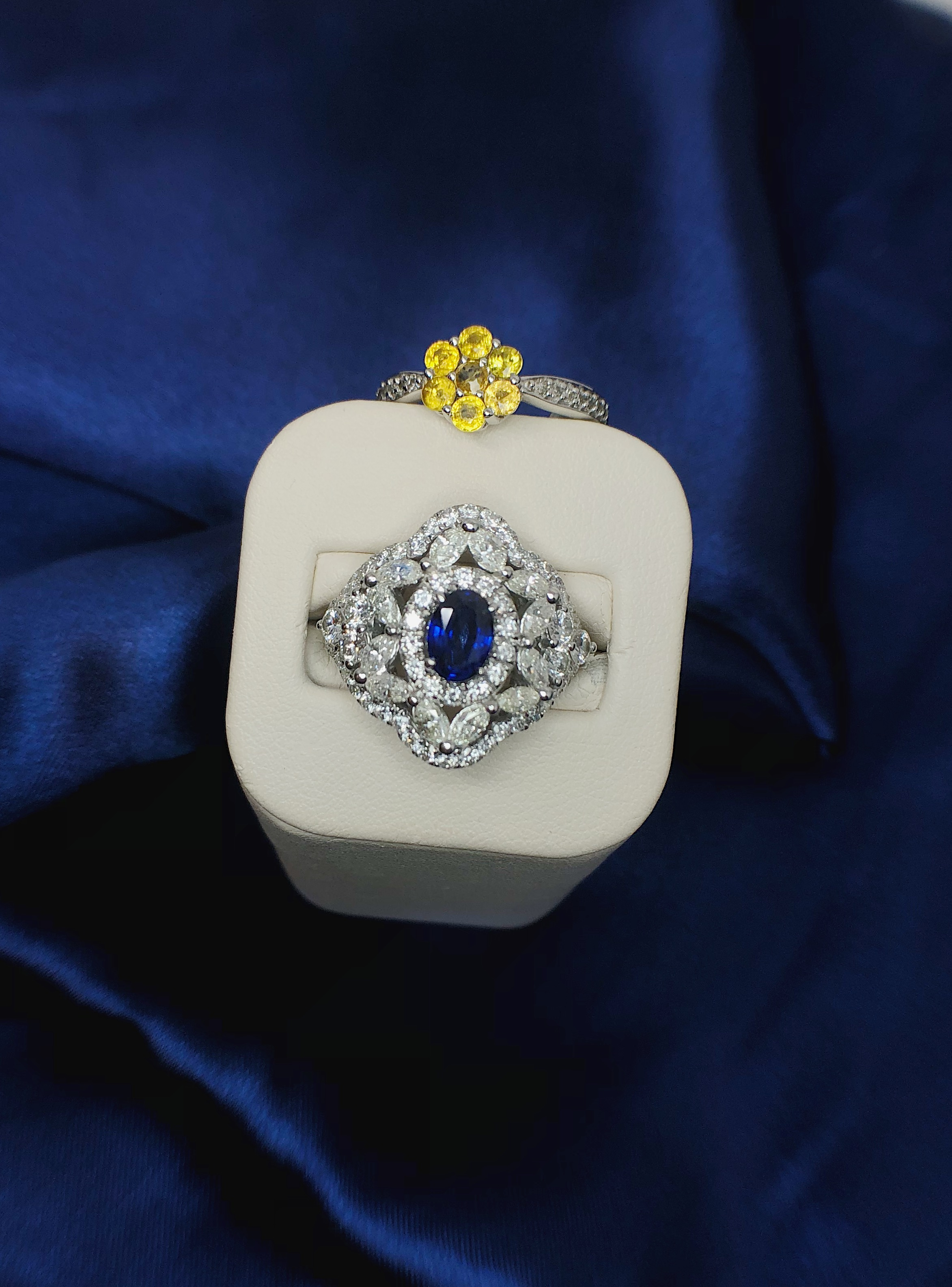 A stunning sapphire ring surrounded by diamonds… and a YELLOW sapphire ring on top!