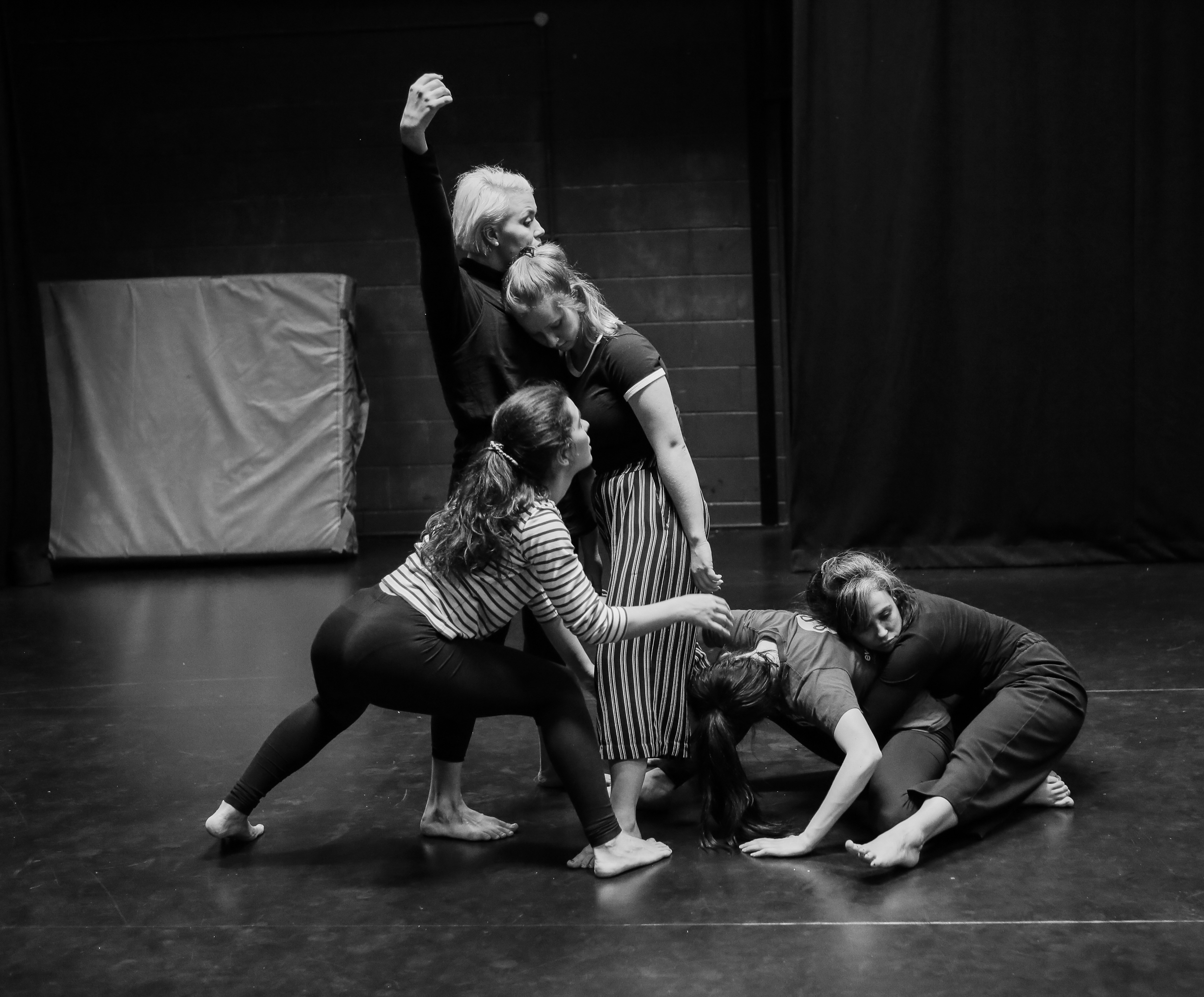 A workshop ensemble engaged in physical theatre exercises.