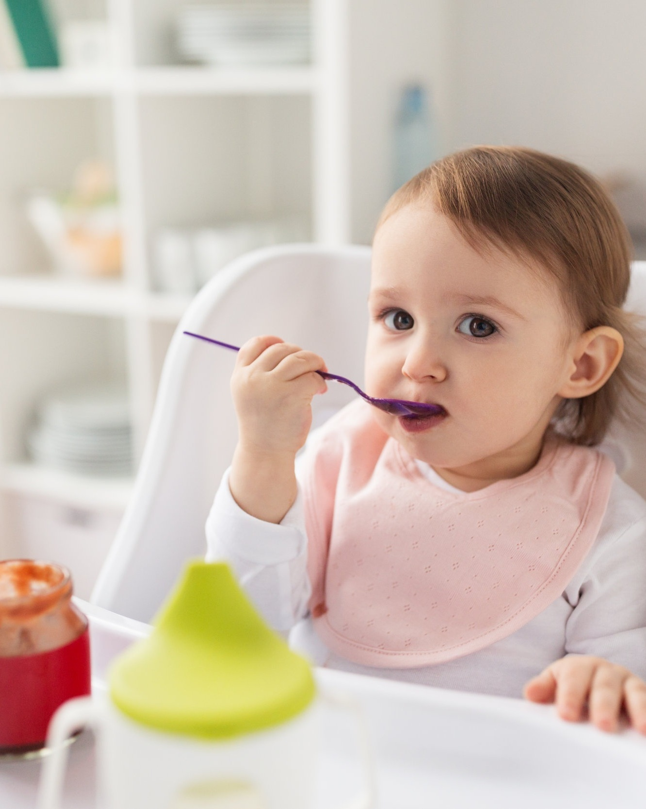 baby-girl-with-spoon-eating-puree-from-jar-at-PJTFBNU.jpg