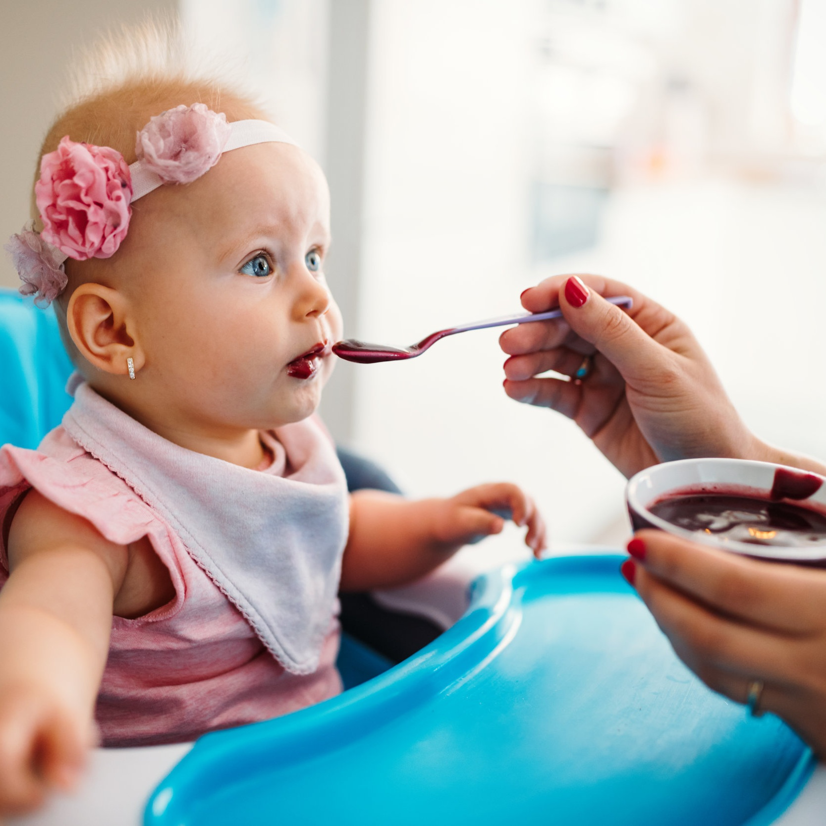 mother-feeding-baby-with-spoon-indoors-ZGAH9Q8.jpg