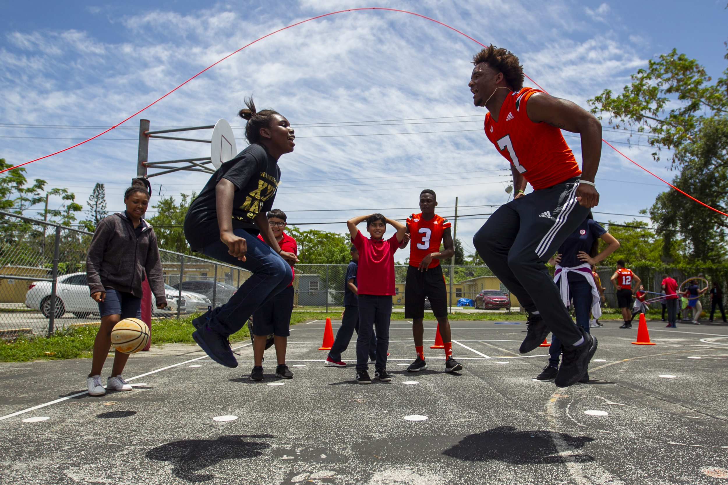 Karis Bellomy, left, jumps rope with University of Miami Hurricane player Brian Hightower (7) at Tucker Elementary School in Coconut Grove on Wednesday, May 23, 2018. The players participated in a day of community service at Tucker Elementary where they interacted with kids by throwing footballs, playing basketball and hula hooping.