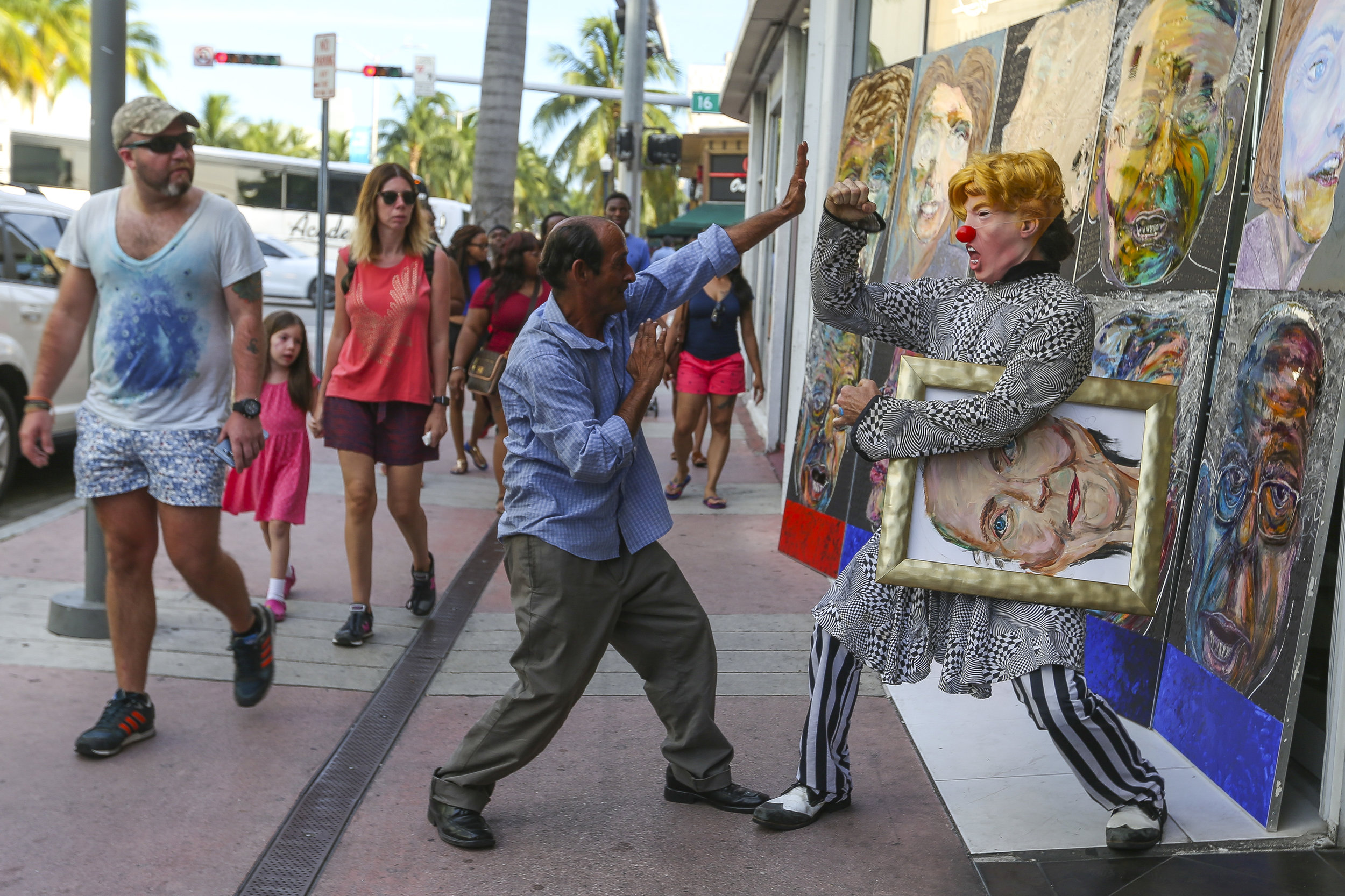 A clown posing as presidential candidate Donald Trump play fights with a pedestrian in Miami Beach outside of artist Huong's studio on Friday, July 8, 2016.