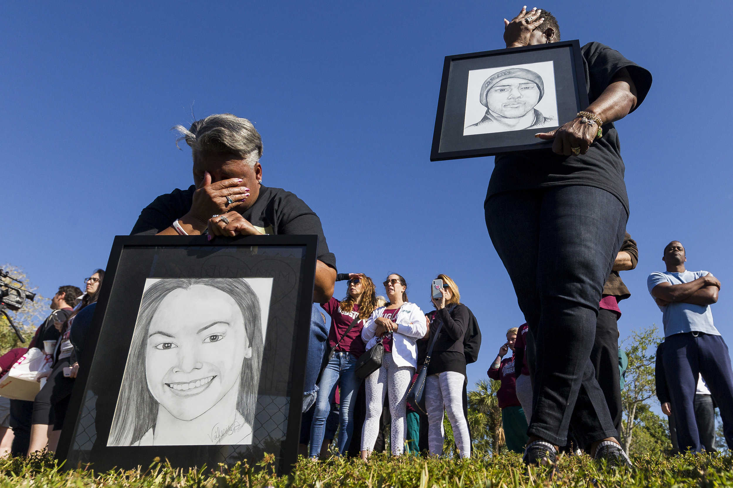 Pat Gibson, left, and Valerie Davis cry while holding drawings of two of the victims killed in the Parkland shooting during the one-month anniversary of the incident outside Marjory Stoneman Douglas High School on Wednesday, March, 14, 2018.