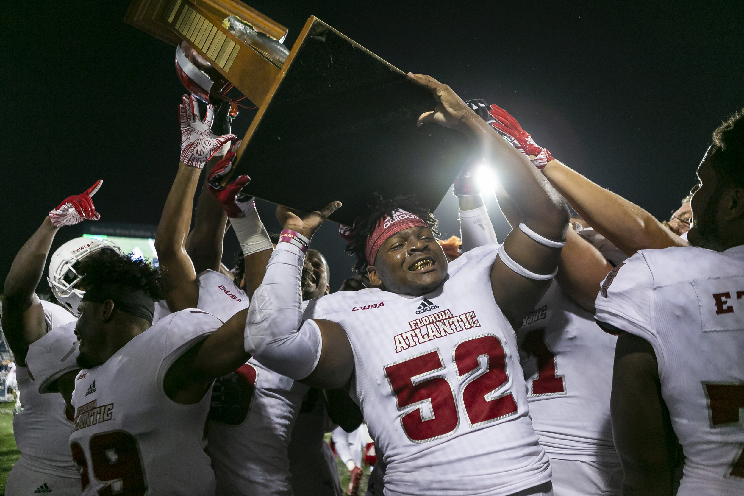FAU defensive end Jaylen Joyner (52) holds the Shula Bowl XVII trophy after they defeated Florida International University 49 to 14 at the Riccardo Silva Stadium in Miami on Saturday, November 3, 2018.