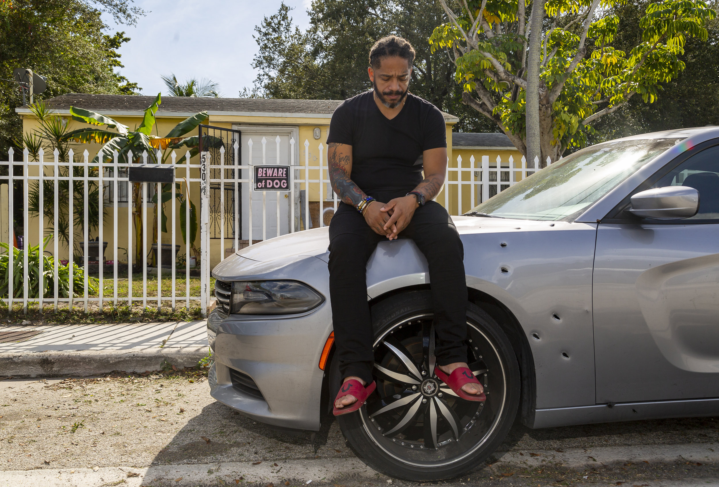 Free Rene Balbona, 39, a youth pastor, sits on his car in front of his home in Little Haiti on Saturday, January 19, 2019. Balbona's car and home were sprayed with bullets when his house got shot on November 28, 2018. Balbona's son, Isaiah, was killed on December 28, 2018 inside a different car in Opa-locka.