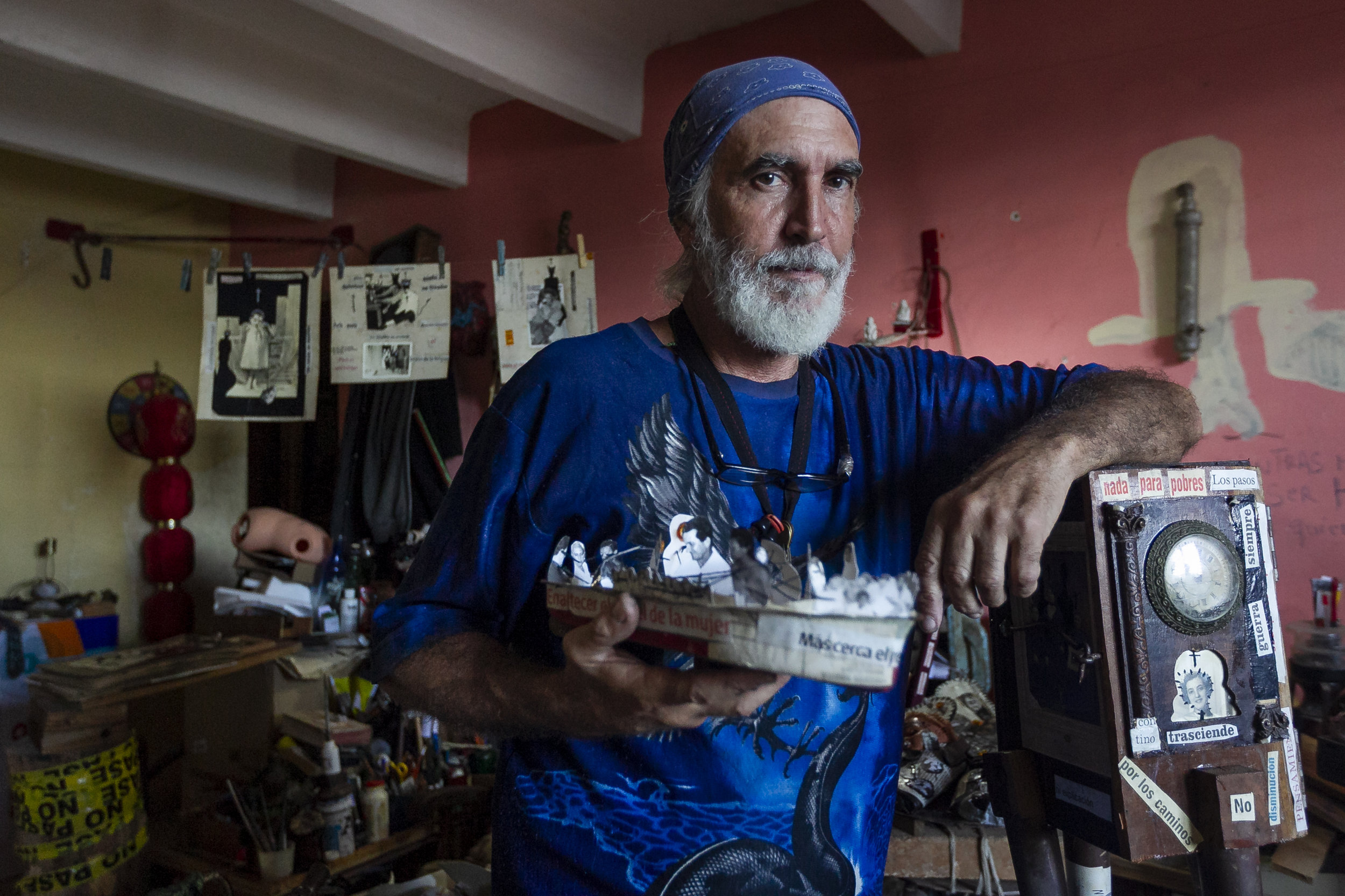 """Jorge Alberto Hernandez Cadi, a Cuban outsider artist who lives in Alamar, holds a boat he created from paper and old photographs. Hernandez is known as """"El Buso"""" (the diver) because he scavenges through the trash to find objects for his art."""