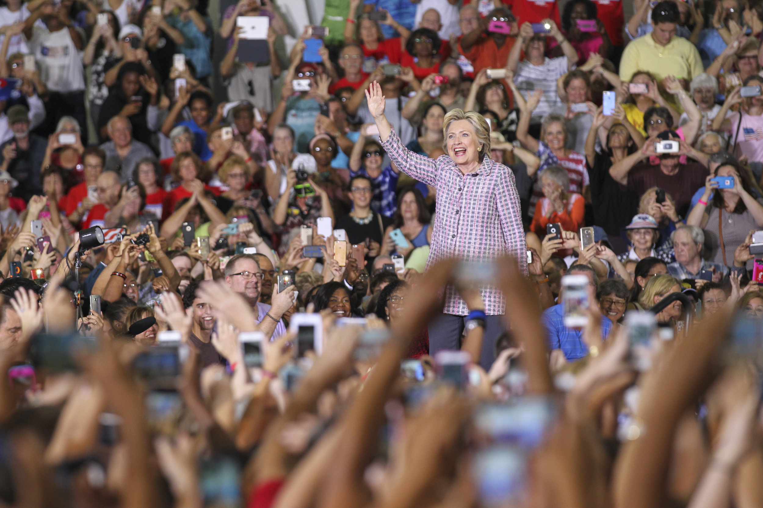 Hillary Clinton waves to supporters after arriving to her political rally at a Coral Springs gymnasium on Friday, September 30, 2016.