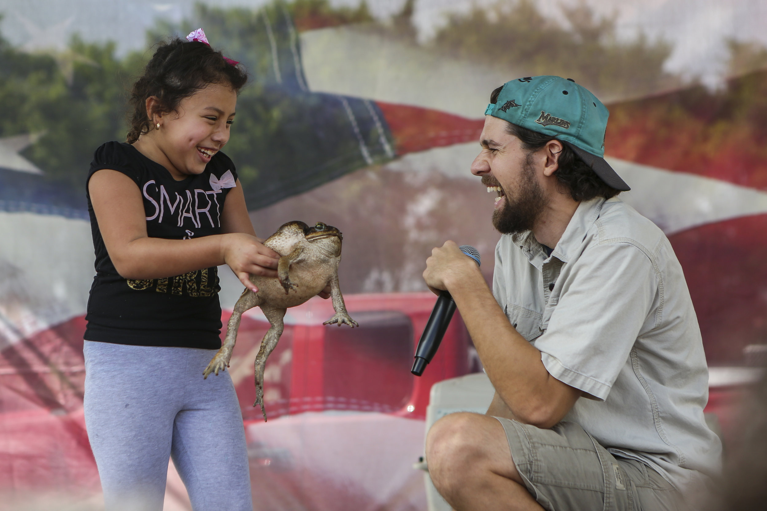 Ashley Castillo, 6, and Raul Tamayo, 24, react while Castillo holds a cane toad during the 29th annual Dodge City Christmas Party in Richmond West on Sunday, December 18, 2016. More than a 1,000 underprivileged kids throughout South Florida were expected to attend the event, which featured a variety of rides, a petting zoo and free food.
