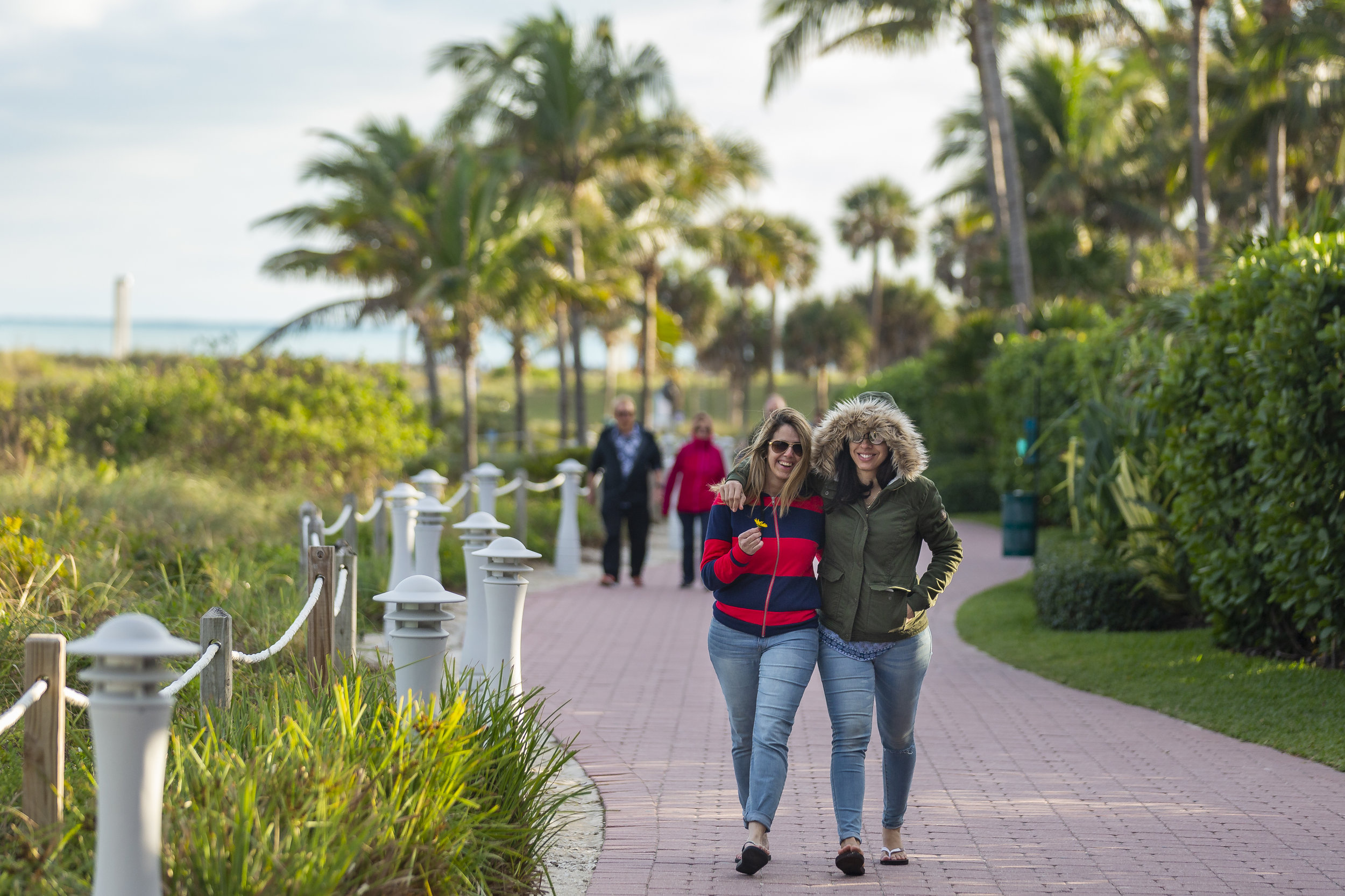 Regina Soares, left, and Rafaela Squiabel, both tourists from Boston, walk down a sidewalk near South Pointe Park Pier in Miami Beach as temperatures drop into the 50s on Monday, Jan. 28, 2019.