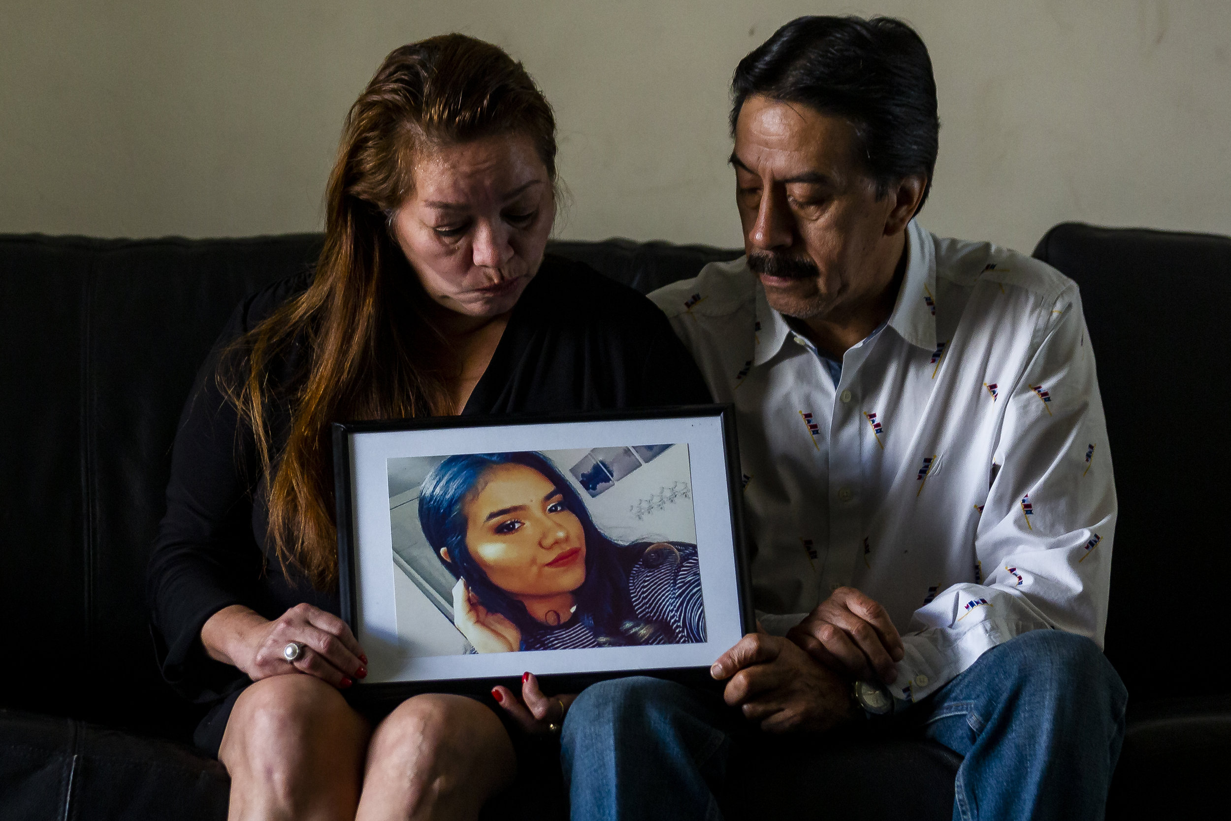 Gina Duran, left, and her husband, Orlando Duran, look at a photo of their daughter Alexa Duran at their home in Miami, Florida on Sunday, December 23, 2018. Alexa Duran, 18, was driving her father's car the day the FIU bridge collapsed. She was one of six people who died as a result of the accident.