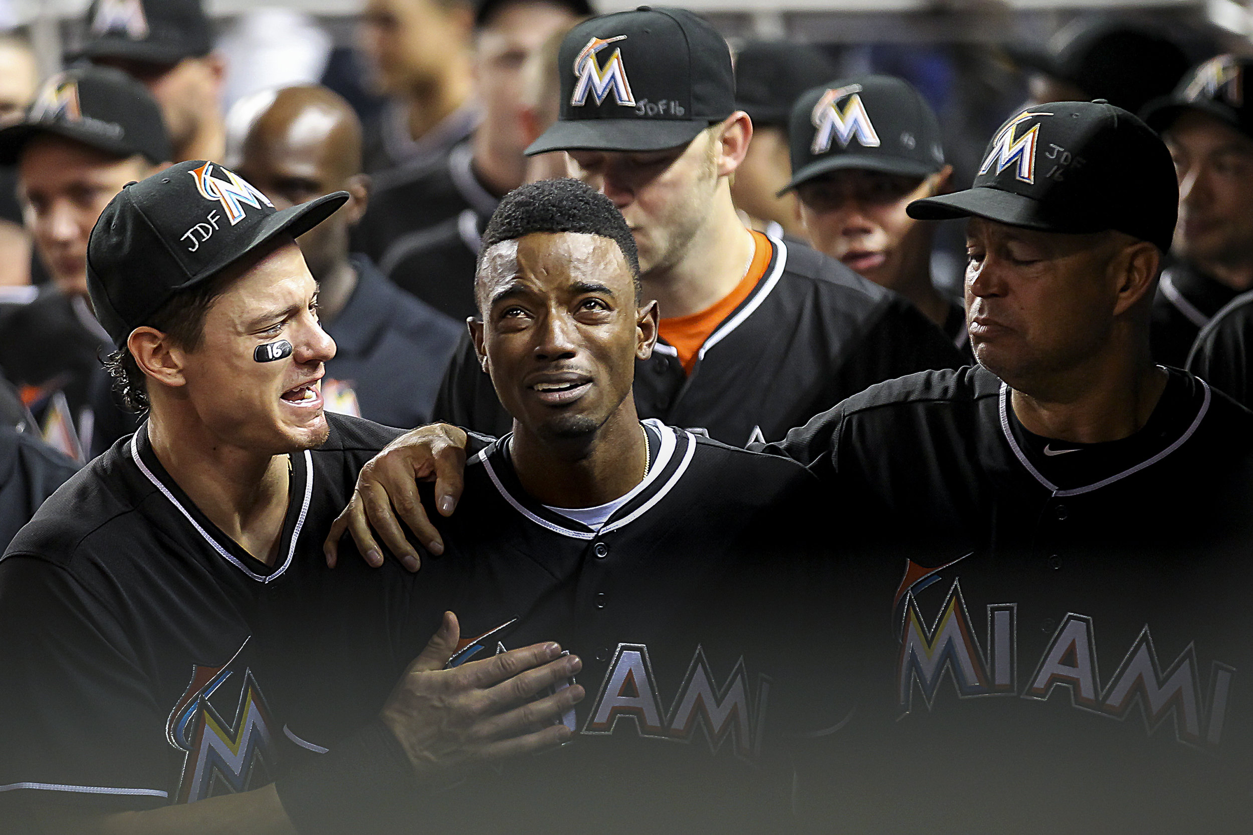 Miami Marlins' Dee Gordon (9), center, gets consoled by Derek Dietrich (32), left, after hitting a home run during the first inning of a baseball game against the New York Mets at Marlins Park in Little Havana on Mon., Sept. 26, 2016. This is the first game the team played after the death of their pitcher Jose Fernandez.