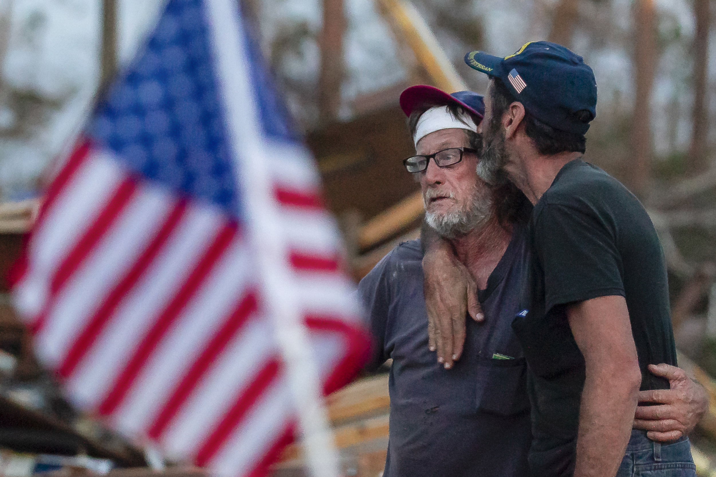 Carl Kuhn, 56, kisses his friend, Mickey Fox, 61, next to what remains of the trailer Fox and his wife rode out Hurricane Michael in Calloway, Florida on Saturday, October 20, 2018. Kuhn pulled the Foxes from the ruins of their home during the eye of the storm.