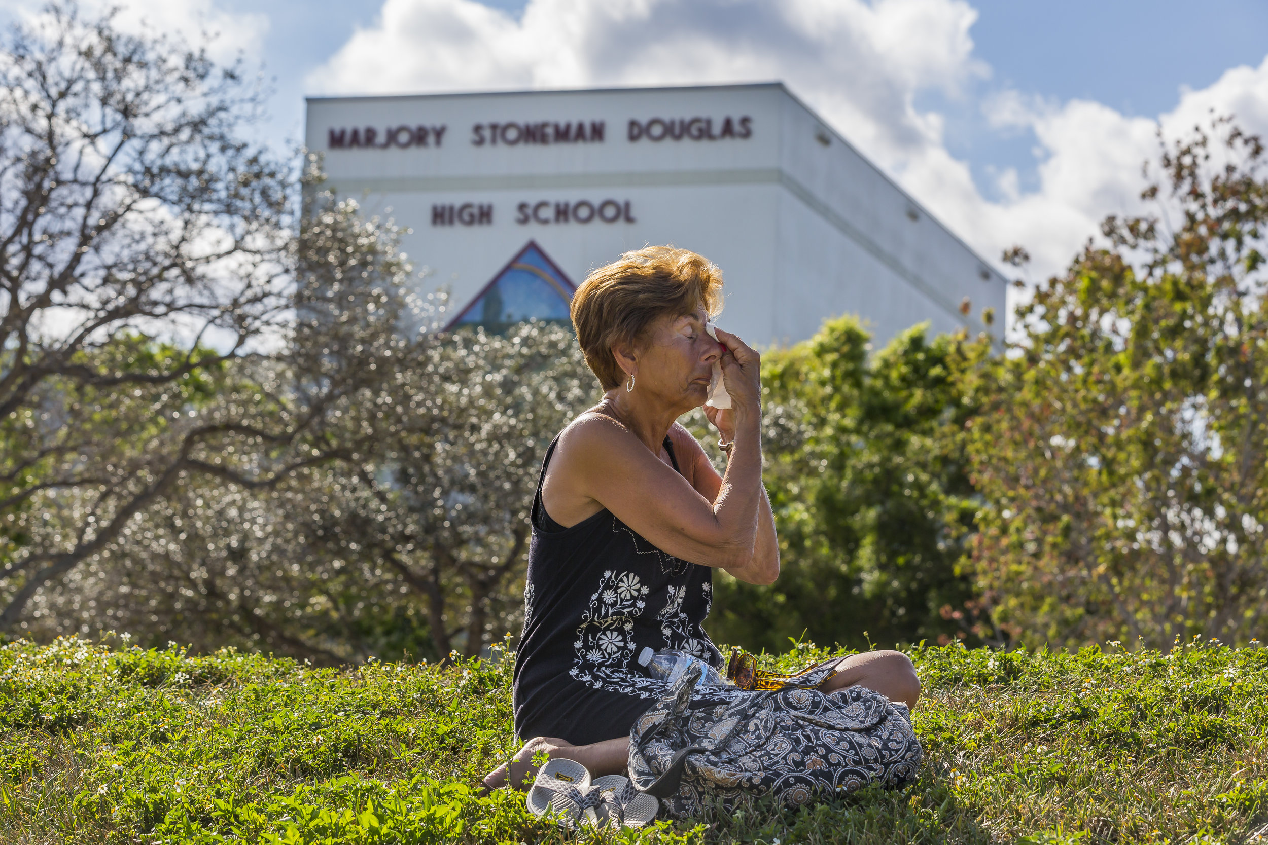 Diane Cappelli wipes tears as she mourns in front of Marjory Stoneman Douglas High School in Parkland, Florida on Sunday, February 18, 2018. A gunman entered the school and killed 14 students and 3 teachers.