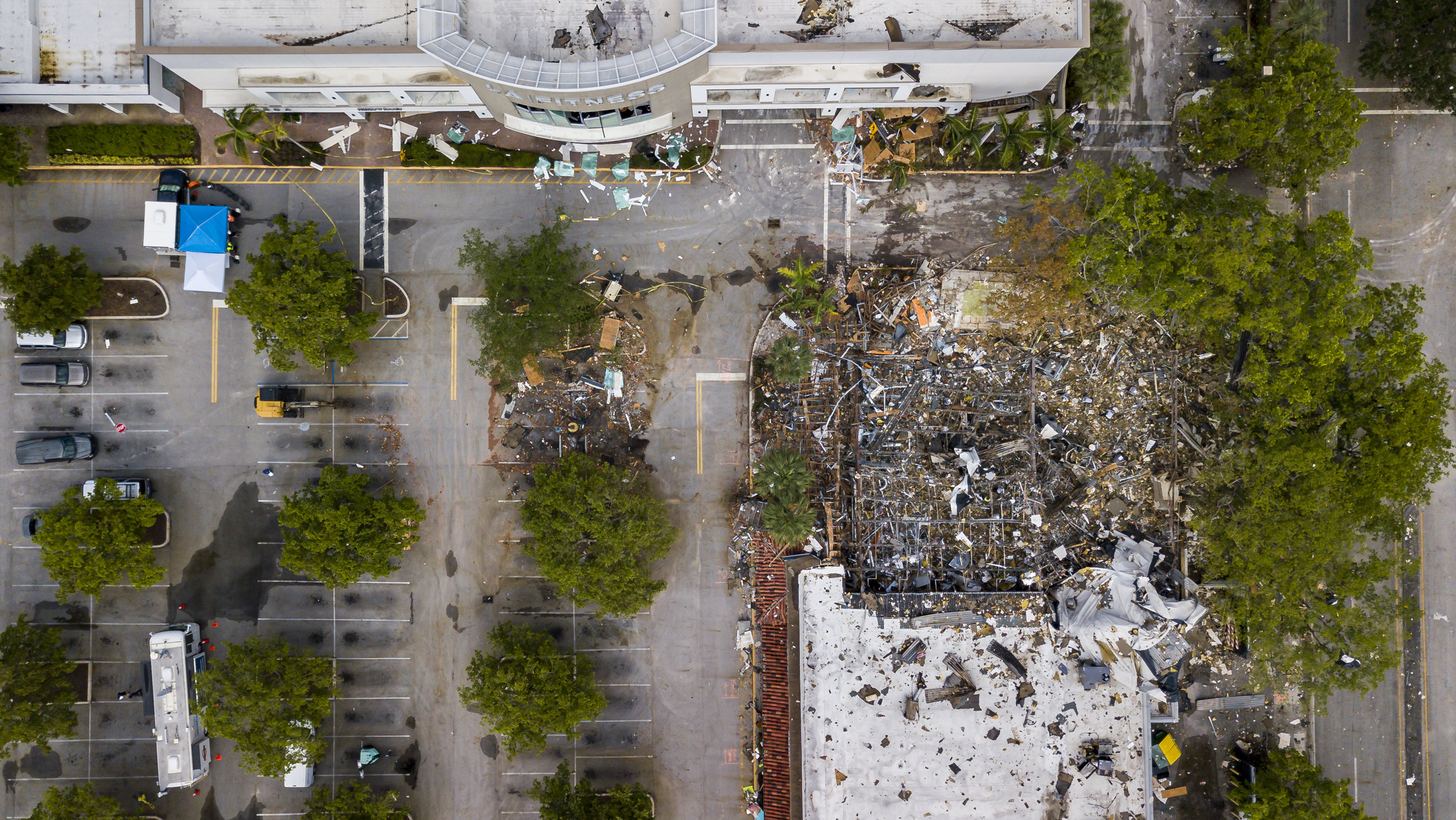 Police work the scene and clear debris three days after an explosion leveled The Fountains shopping plaza in Plantation, Florida on Tuesday, July 9, 2019. The explosion, which happened on July 6, 2019, injured 23 and left a pizza parlor demolished.