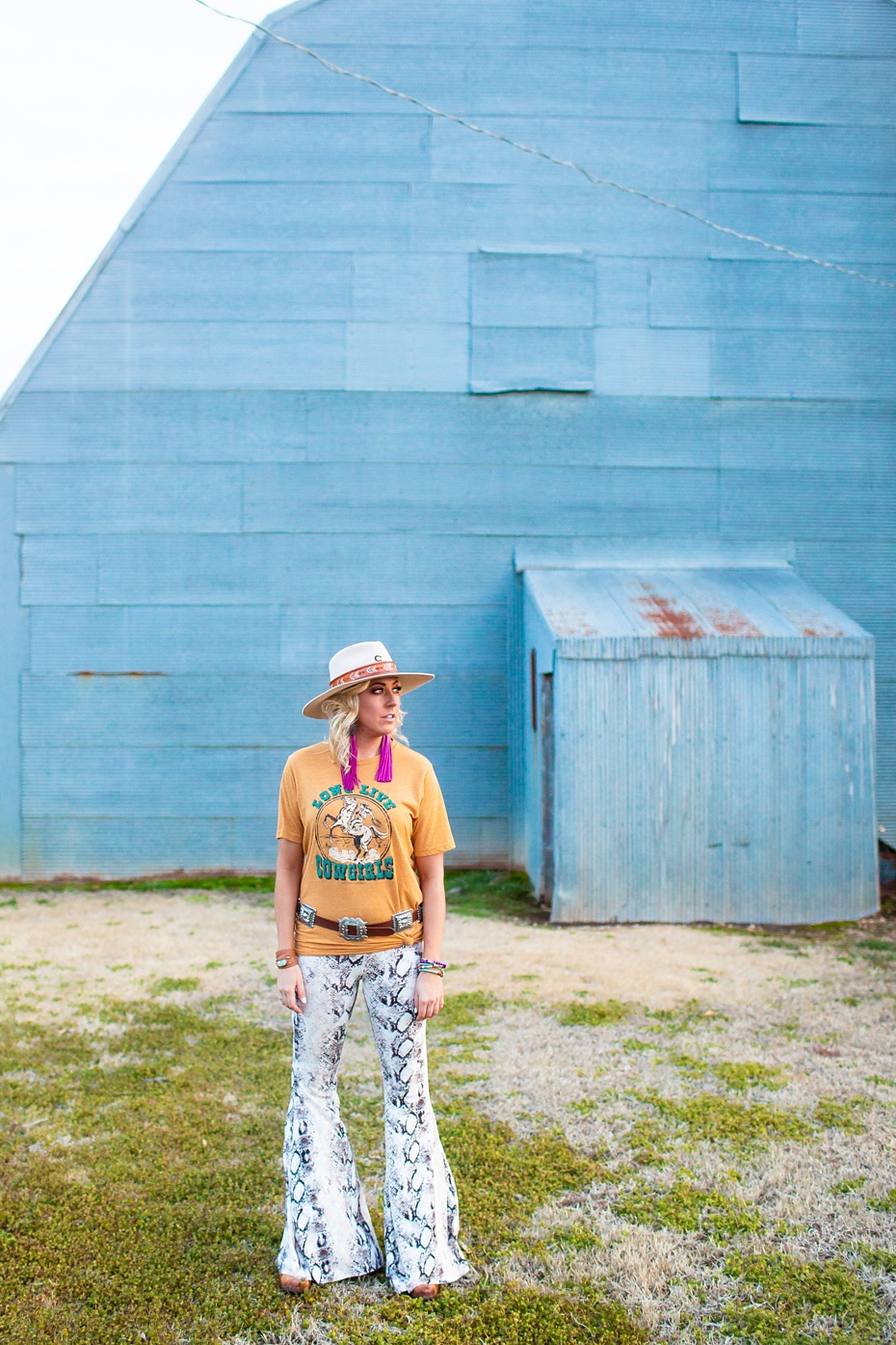Graphic tee, concho belt and snakeskin bell bottom pants are from  Baha Ranch Western Wear   Fringe earrings are from  Saddle Tramp Brand   Felt highway hat is from  Charlie 1 Horse  and the hat band is from  Nifty Gypsy Originals