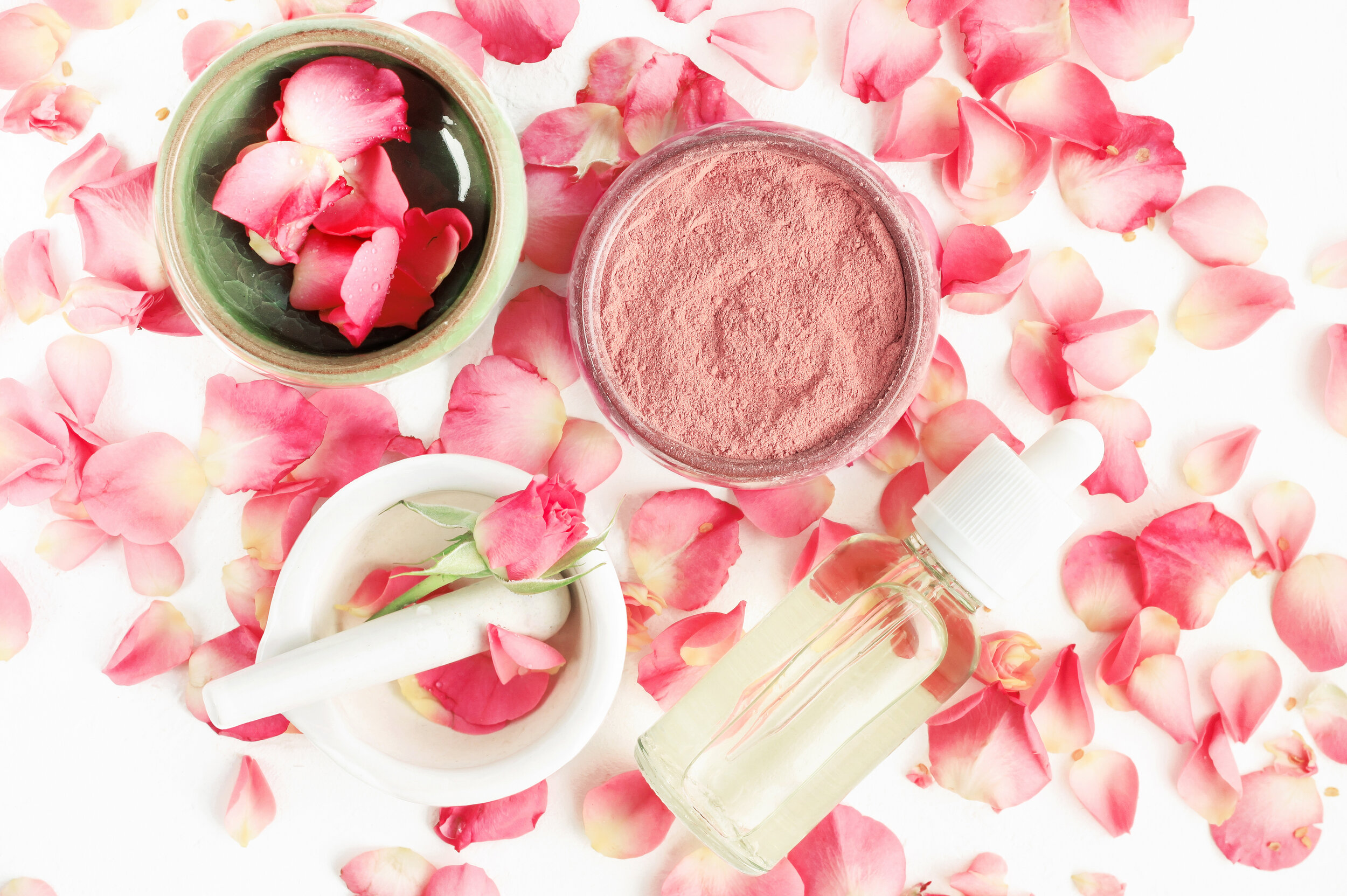 Top view botanical skincare home spa treatment with pink petals, rose blossom, clay face mask, bottle of essential oil.