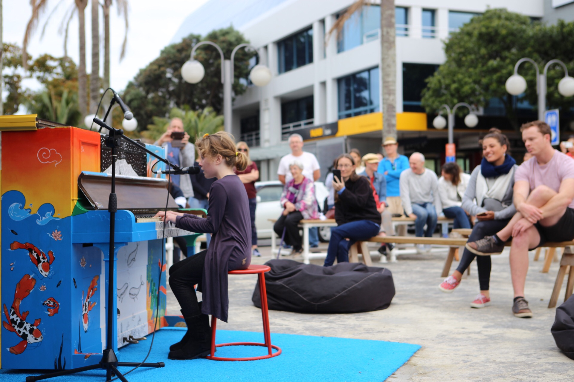 Cara     is well known for her busking performances in Takapuna. She performed at the  Youth Arts New Zealand  showcase of Young Musicians in May 2019 on the public piano that now lives in the blue container.  This piano was gifted to the public space and painted by three artists who designed their artwork based on Takapuna's unique environment with Lake Pupuke, Takapuna Beach and Rangitoto. Youth Arts New Zealand orchestrated the public piano project and facilitated numerous events for young musicians at 38 Hurstmere in May and June 2019.
