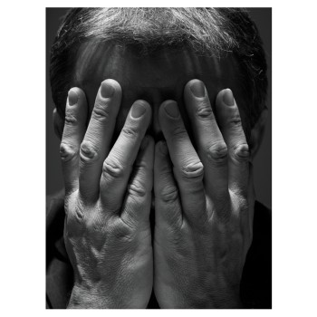 man with hands covering face