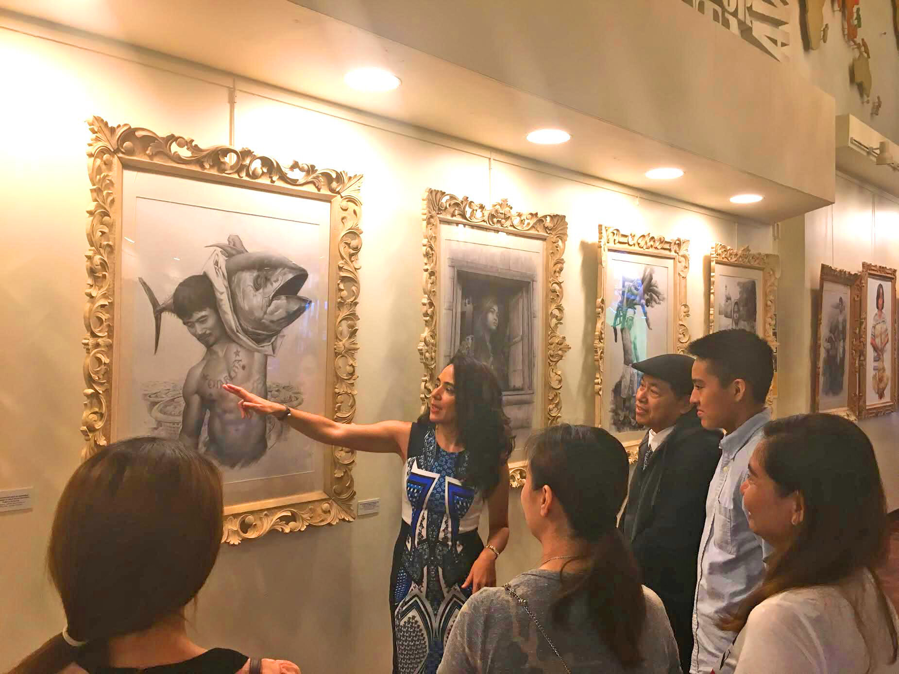 Murga explaining the artworks to the audience at the Philippine Consulate in New York