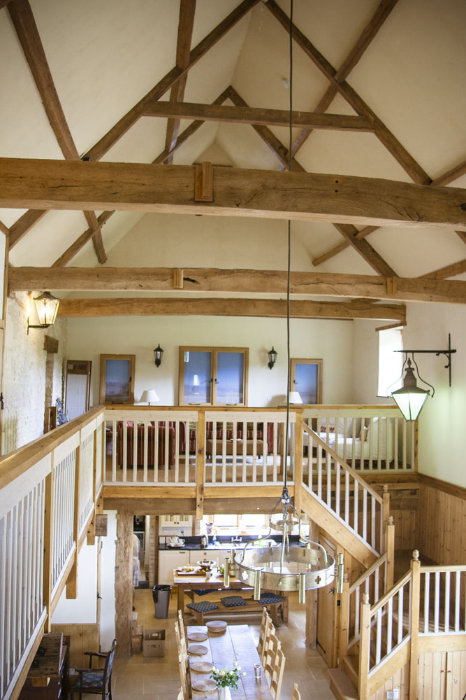 The big barn has a magnificent high timbered roof - With a gallery looking down over an open plan living area, with a stone chimney and wood burning stove. A baronial dining table for 20 stands on a warm flag stoned floor, under a chandelier.