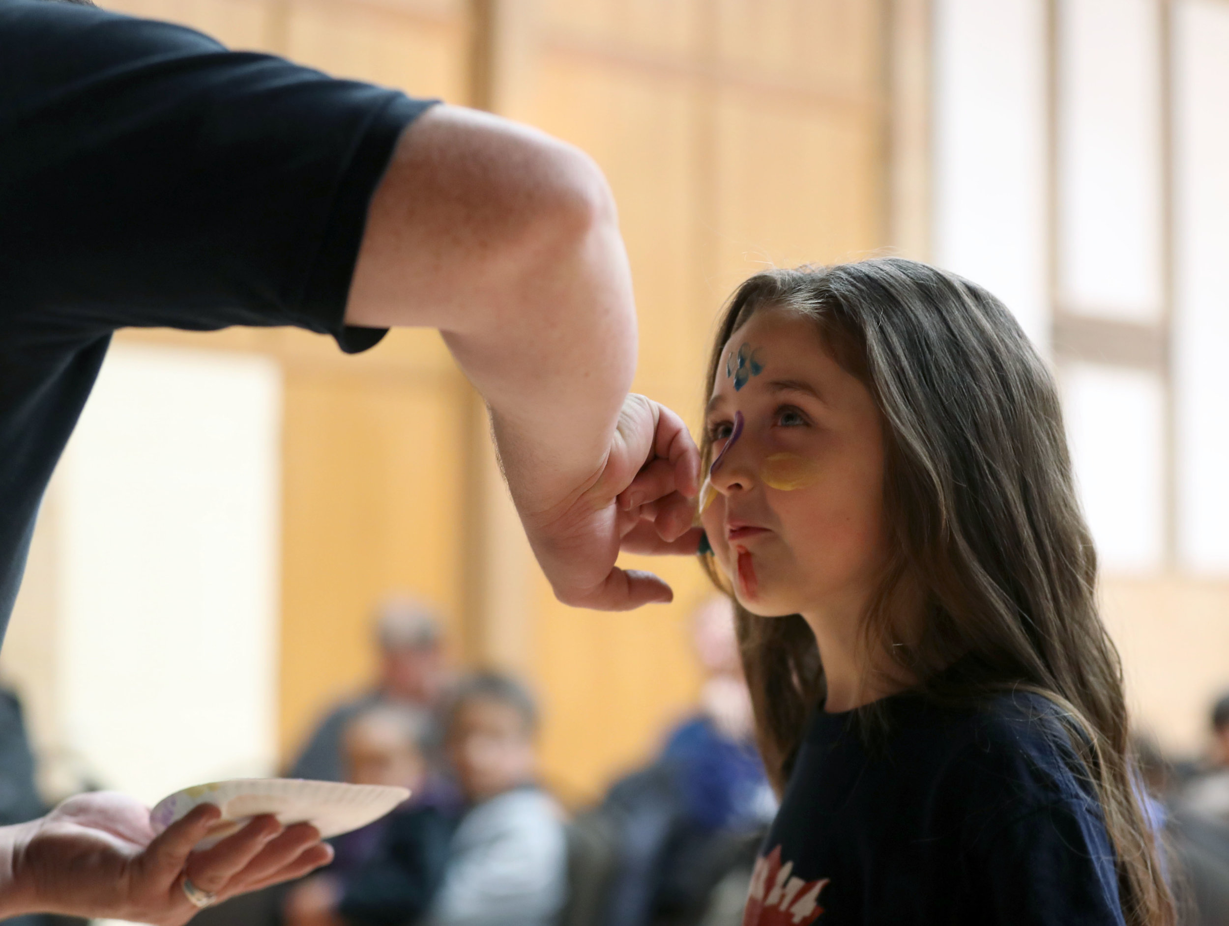 Zhane Johnson uses his hands to paint Vivica Northrup's face as she receives her Bobcat badge at the monthly Pack 274 meeting at First Christian Church in Texas City on Thursday, Nov. 15, 2018. Each color represents a different value and lesson Boy Scouts of America should emulate and learn.