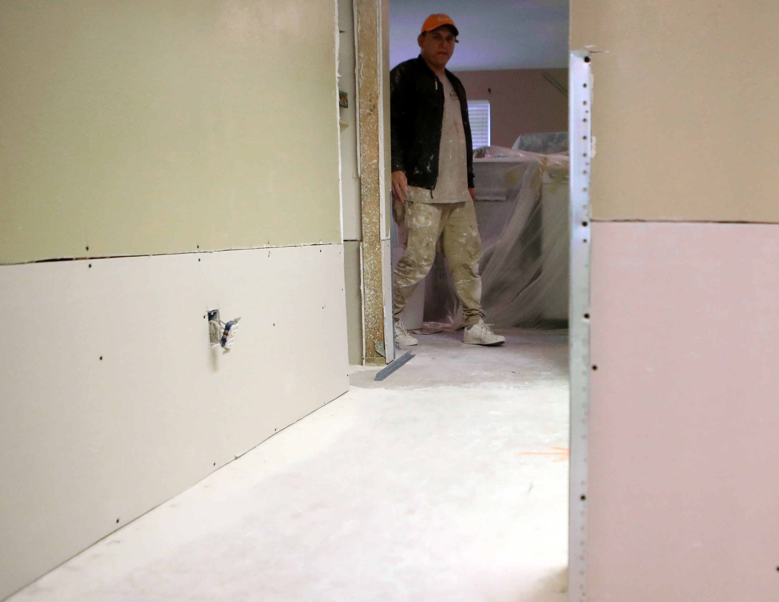 William Campos walks by a hallway with new dry wall while working on the Bishop's home on Tuesday, Jan. 9, 2018. Campos was helping Jesus Lopez with the brunt of the work in the house. It took them about five months to make the inside livable.