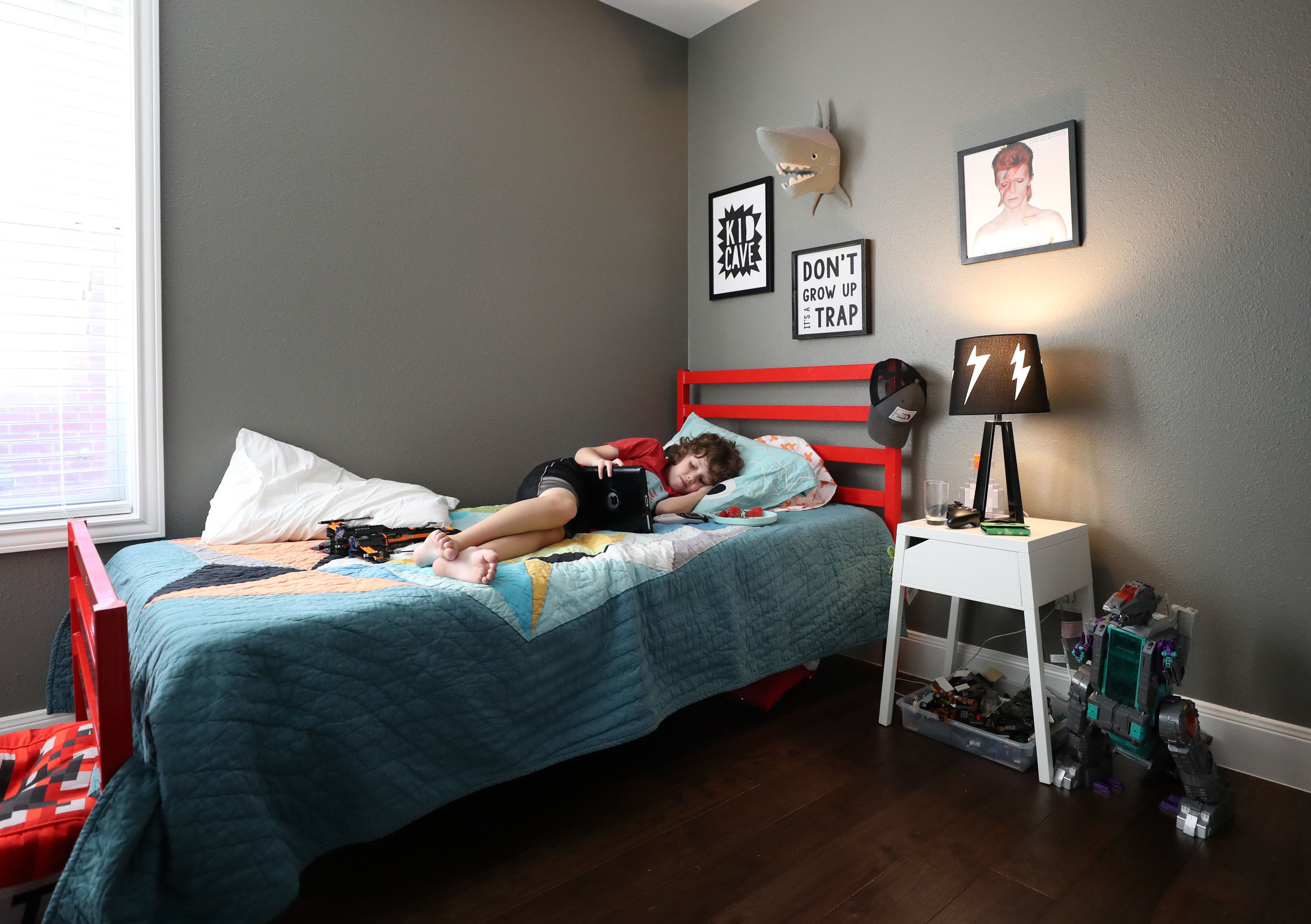 "Joshua Bishop plays with a tablet on his new bed in his home on Wednesday, July 25, 2018. Joshua and his brother, Jacob both started having post-traumatic stress from heavy rain after experiencing Hurricane Harvey, Tiffany said. ""We were surprised how well they got along afterward,"" she said. ""Joshua missed his friends from next door, but they got really close to their grandparents."""
