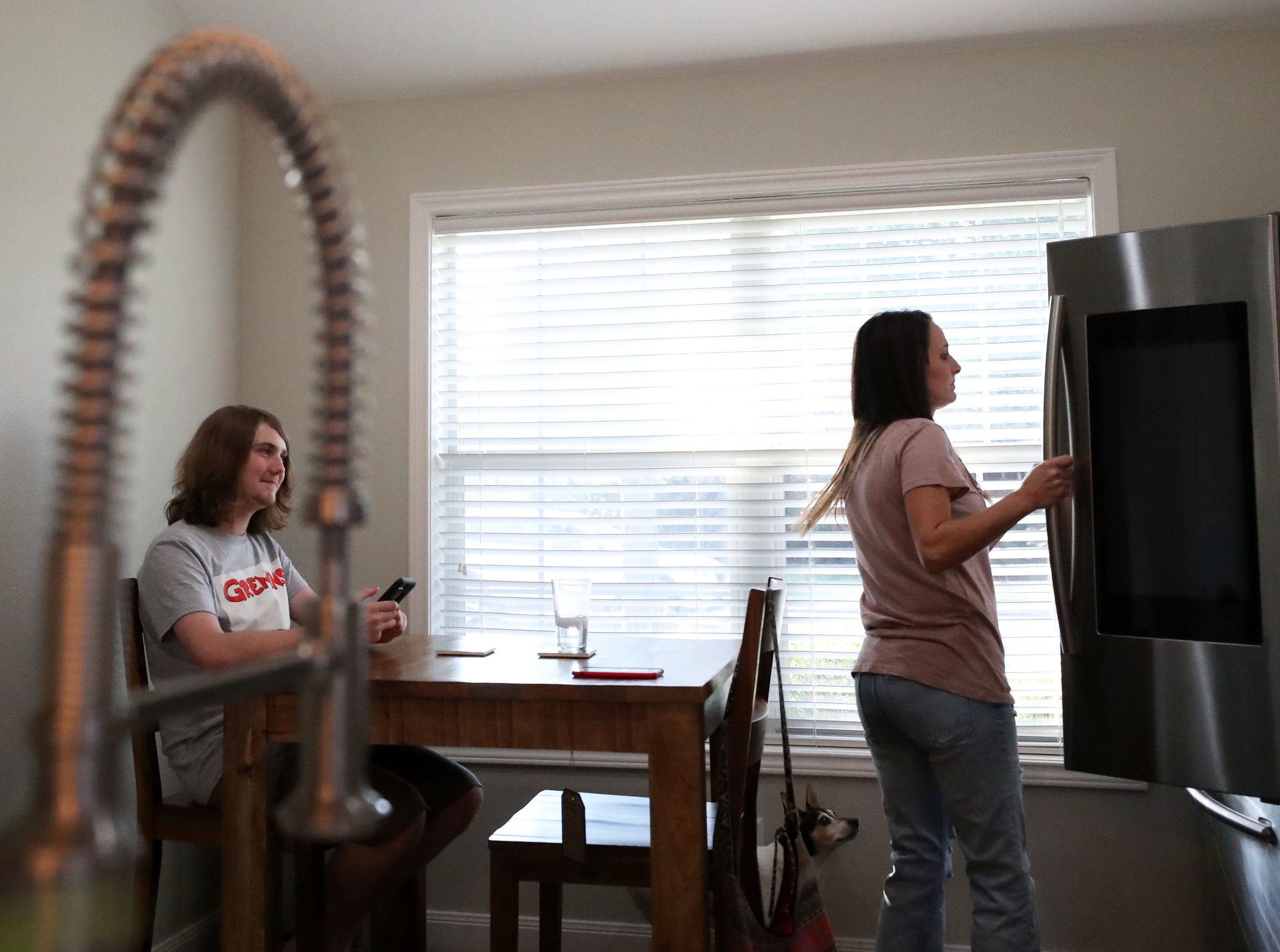 "Jacob Bishop smiles while Tiffany gets dinner ready in their new kitchen on Wednesday, July 25, 2018. ""We had to get used to living in our house together again,"" Tiffany said. ""They adjusted to living with their grandparents and got into a routine there."" Jacob had to be reenrolled into Dickinson High School for his junior year since his address was different last year due to Hurricane Harvey."