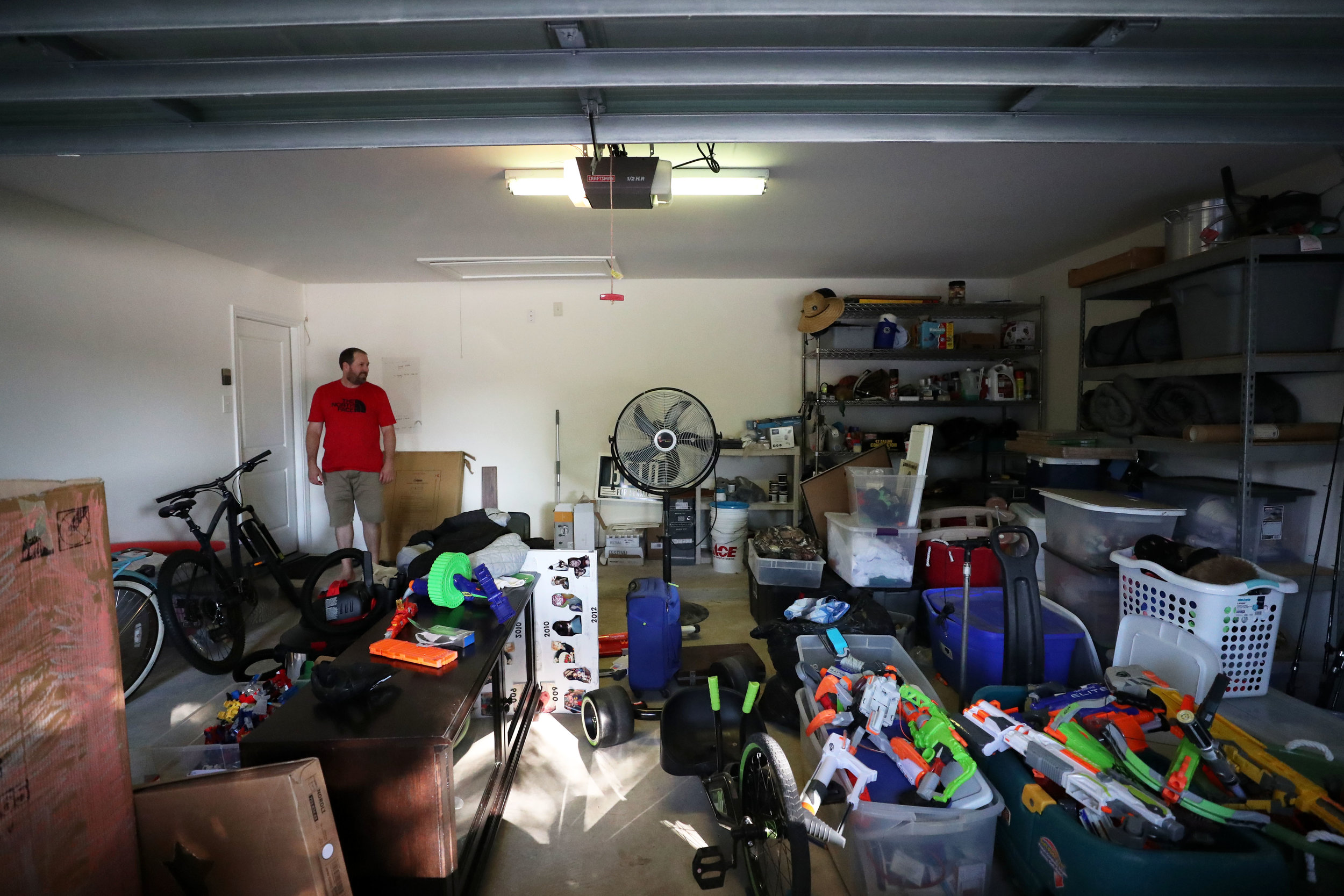 "Jimmy Bishop looks over extra toys, tools, furniture and clothing that not been sorted yet in their garage on Wednesday, July 25, 2018. Jimmy is worried about houses constantly being built around the area without more drainage options being built as well. ""Knowing the process takes that long makes it terrifying for a potential flood,"" Jimmy said. ""But if it does, we are much better prepared with this experience behind us."""