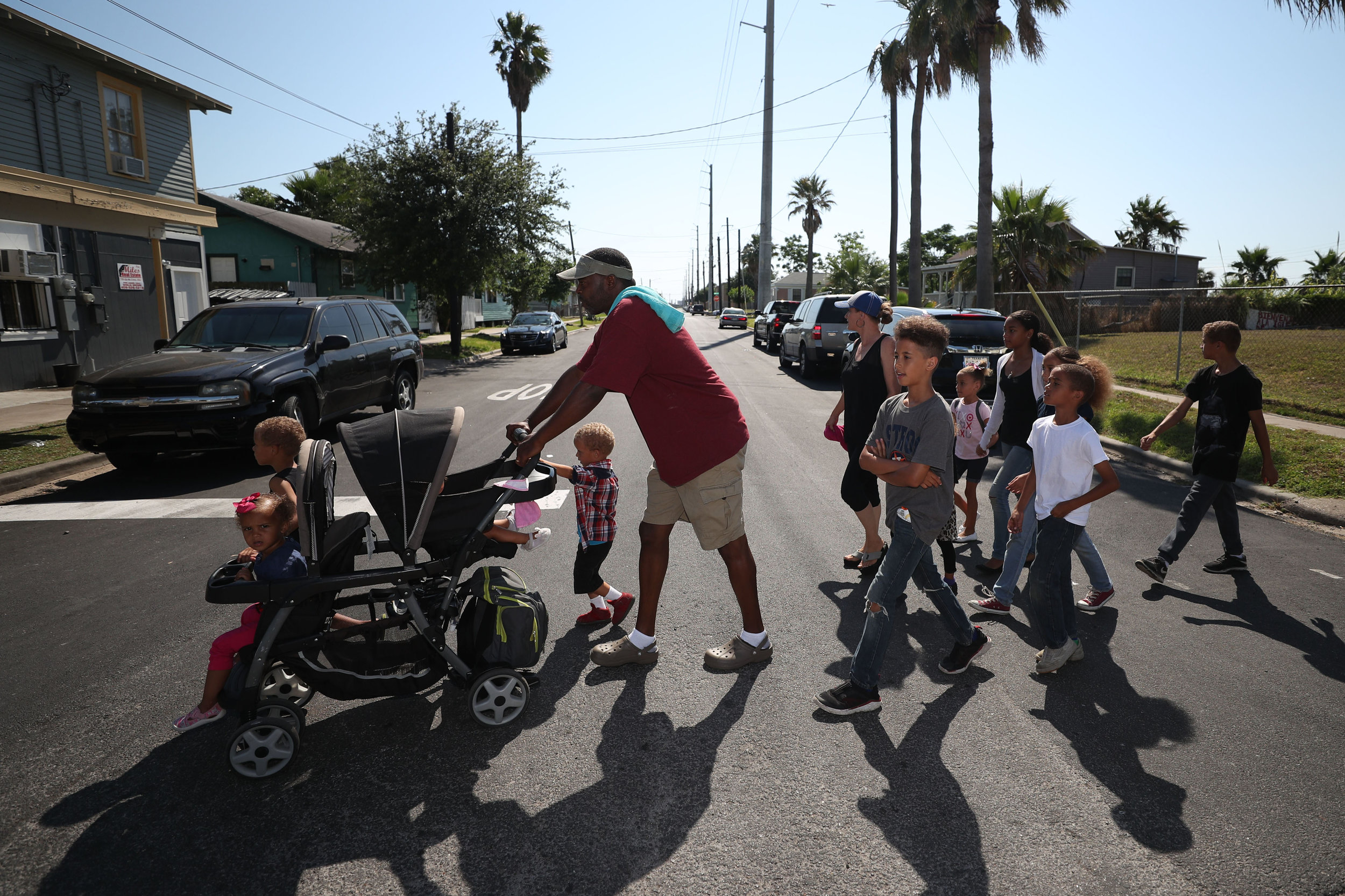 The Whites walk across the street together while on a walk to the Galveston Children's Museum on Wednesday, May 16, 2018. In their free time, the Whites often take trips to museums and the beach for some afternoon entertainment, but they always walk since they do not own a car.