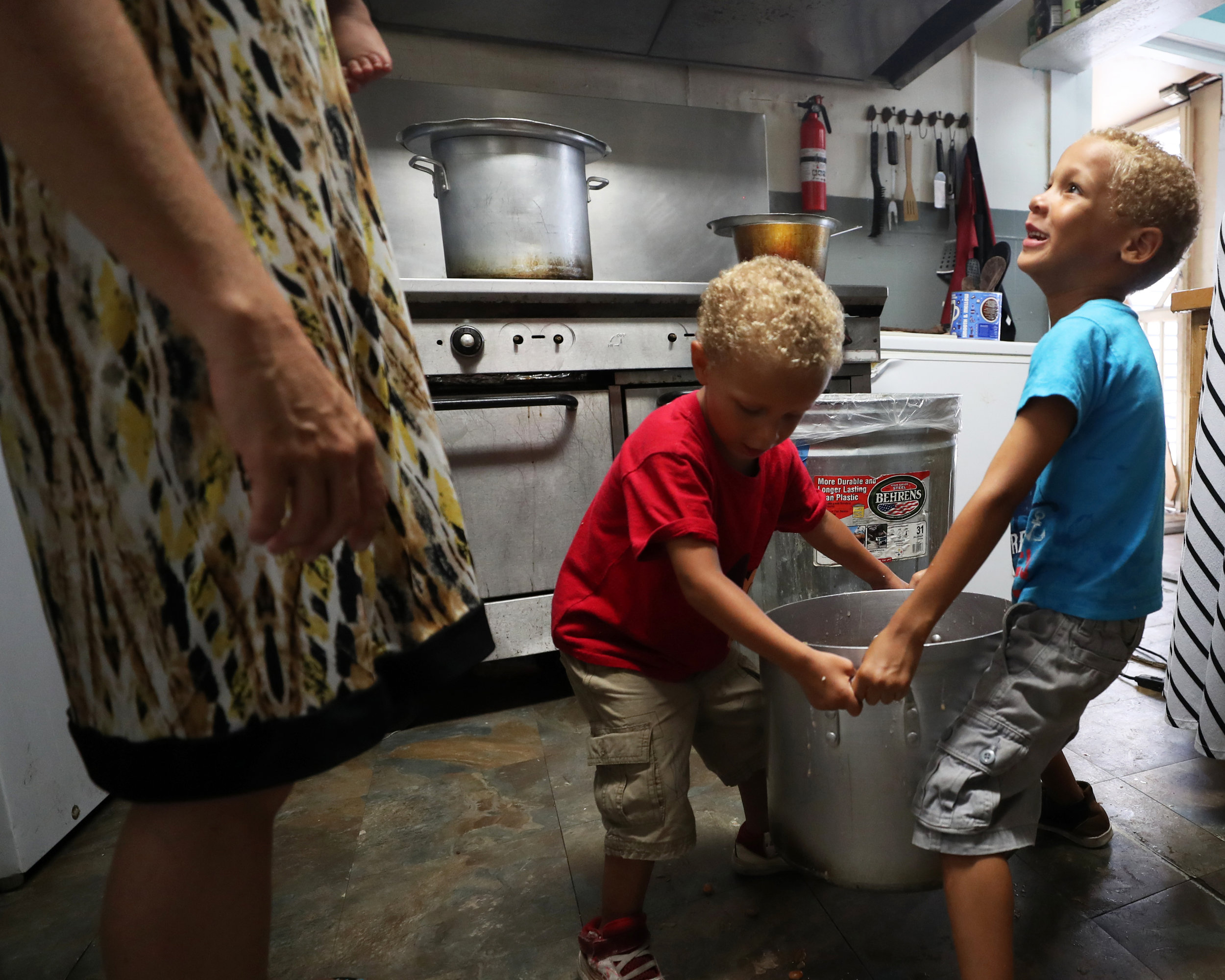 Kaleb White looks up at Karla White while lifting a pot of beans with his brother, Kamron at the Streetscape Café on Thursday, May 24, 2018. The children enjoy helping Karla prepare breakfast and lunch at the café.