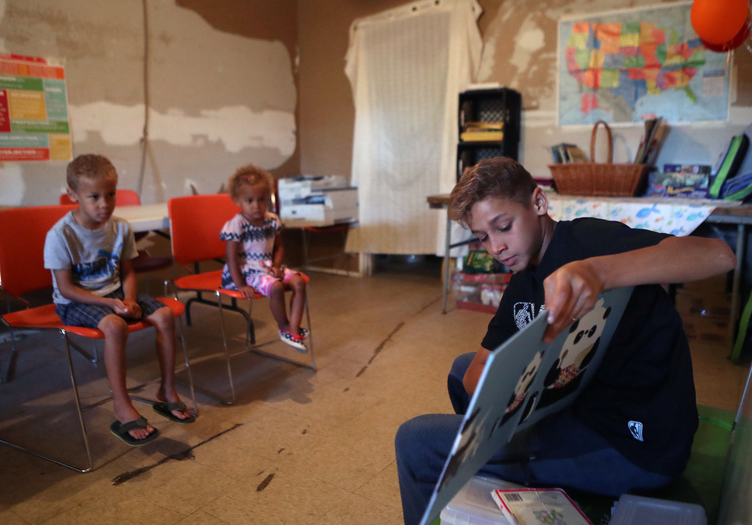 Kemuel White reads to his siblings, Kaleb and Kendra, during home school on Thursday, May 10, 2018. The children are homeschooled in a room at the back of the café. Many of the older children help their younger siblings while educating themselves with a plethora of books and worksheets.
