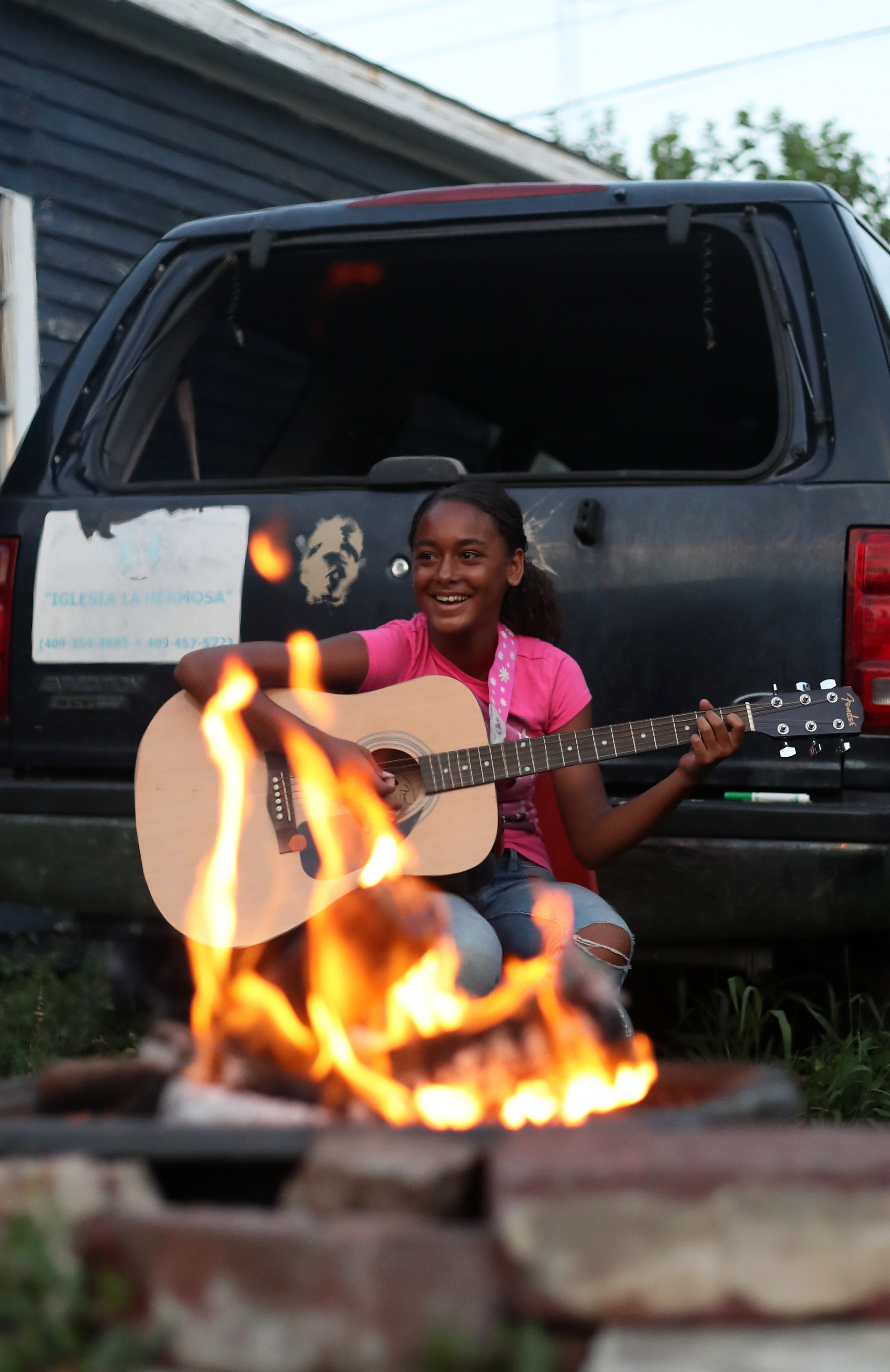 Keturah White smiles while playing the guitar at a family bonfire at home on Tuesday, June 5, 2018. Keturah often leads songs for her siblings as they sing together around the fire.
