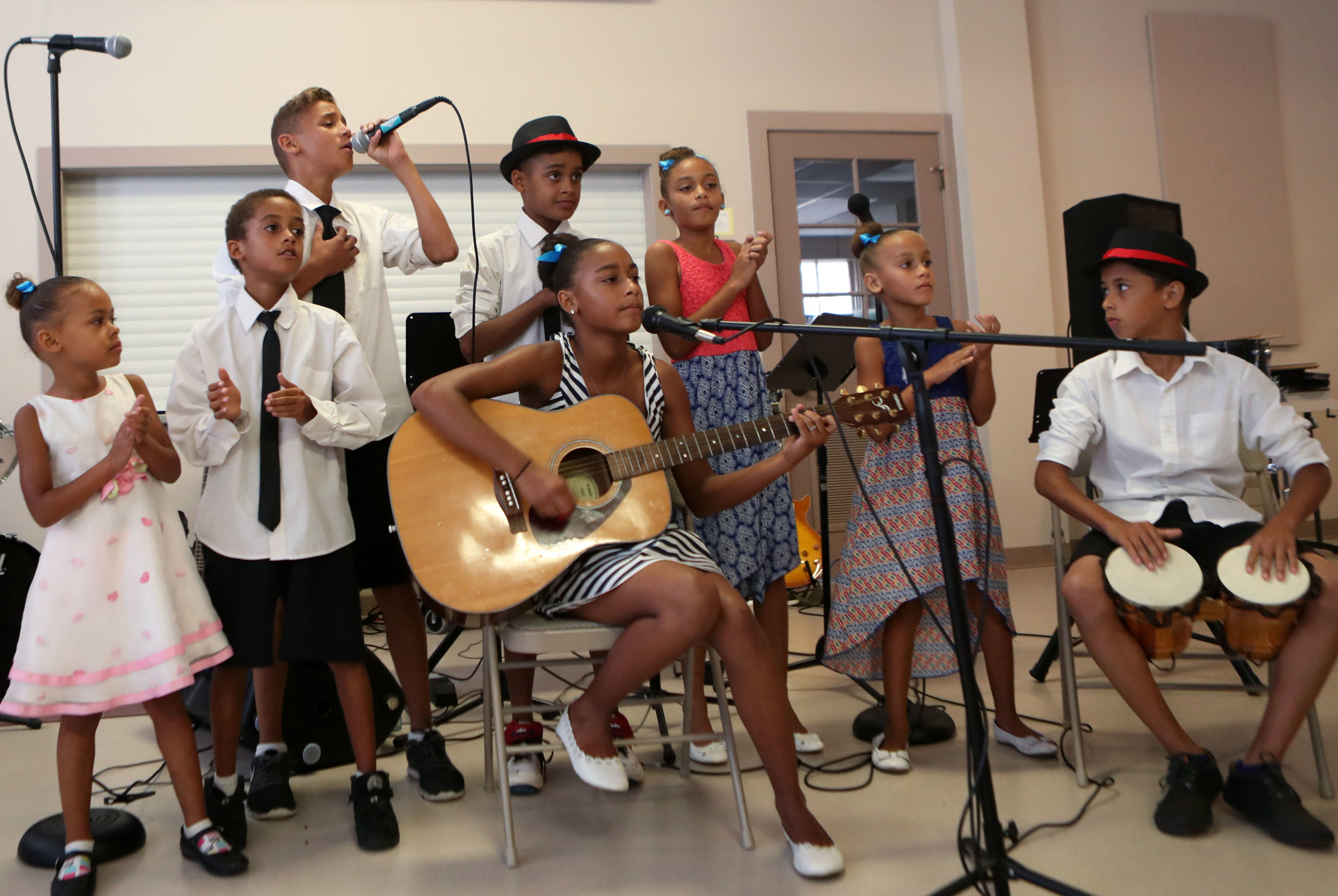 Kemuel White leads the K White family band as they perform a song for an audience at the First Lutheran Church in Galveston on Thursday, June 21, 2018. Nine of the children have been given scholarships and attend classes at Fanfare!, which is associated with the church.