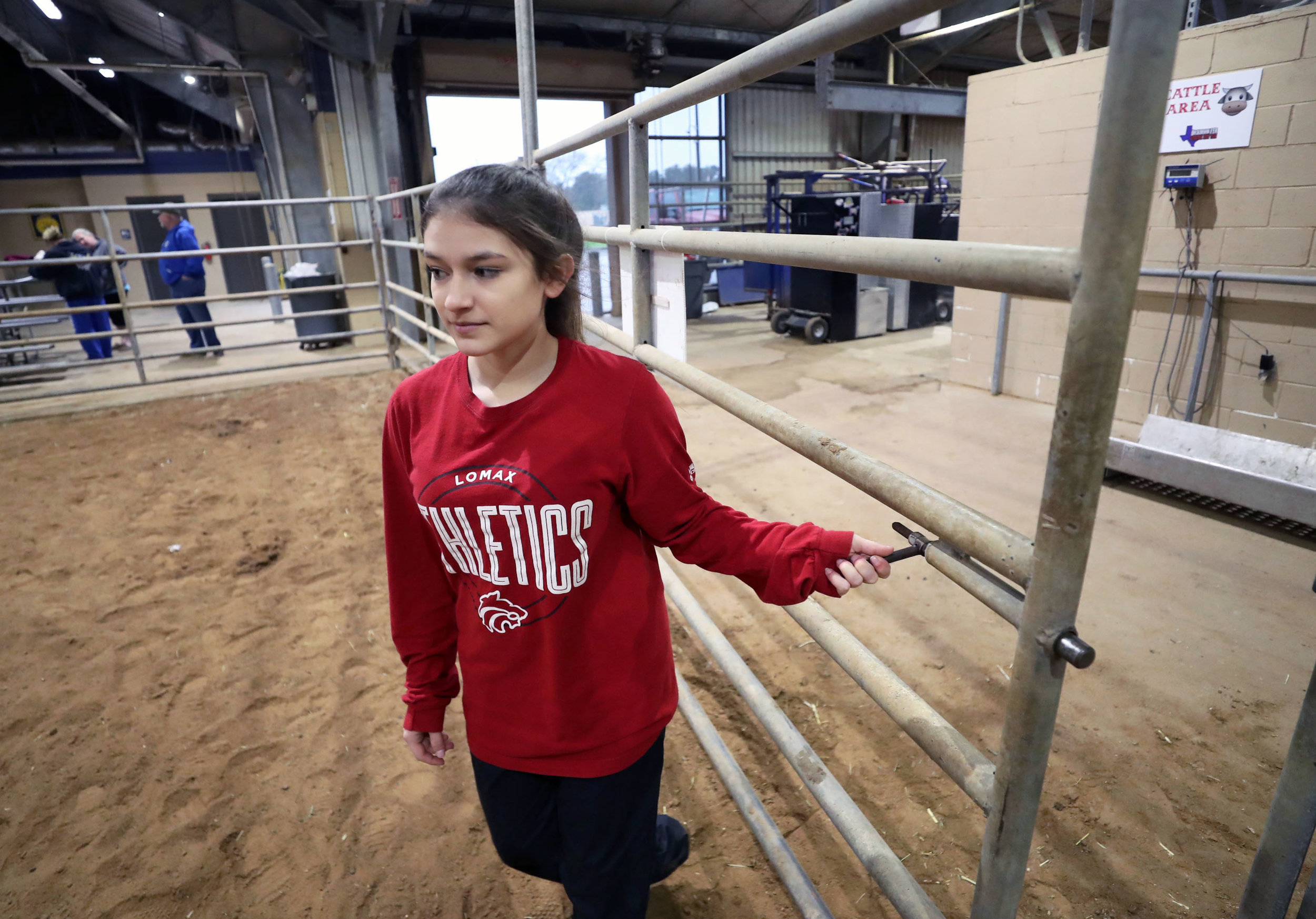Morgan Perez opens the gate for the practice arena at the Dickinson Agriculture Science Facility on Tuesday, Feb. 26, 2019. Students can use the arena to practice how they will show their various livestock at the Galveston County Fair and Rodeo.