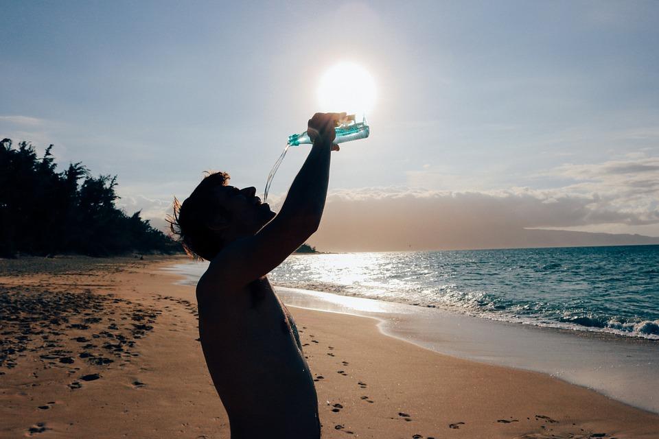 man-drinking-water-on-beach.jpg