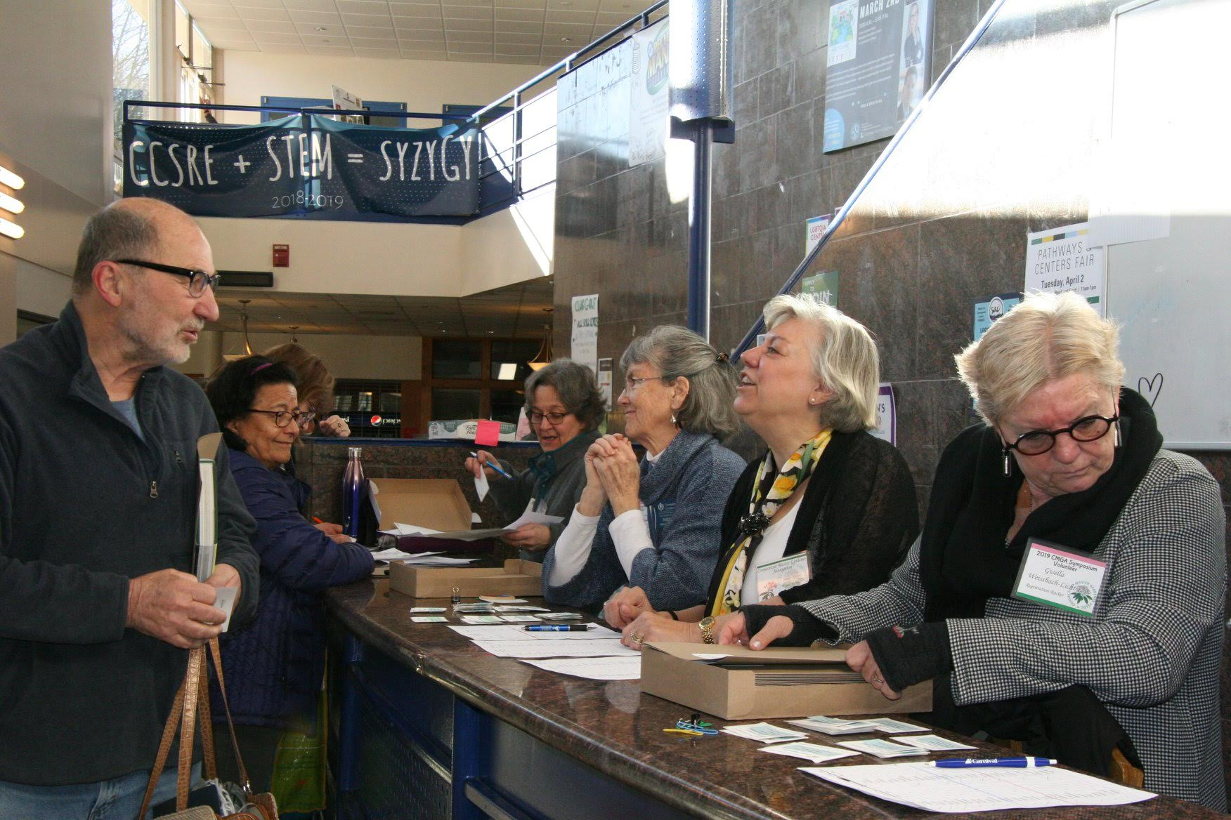 Registration chair Paul Russo behind the desk (far left) & Susan Turner (2nd from right) along with volunteers.