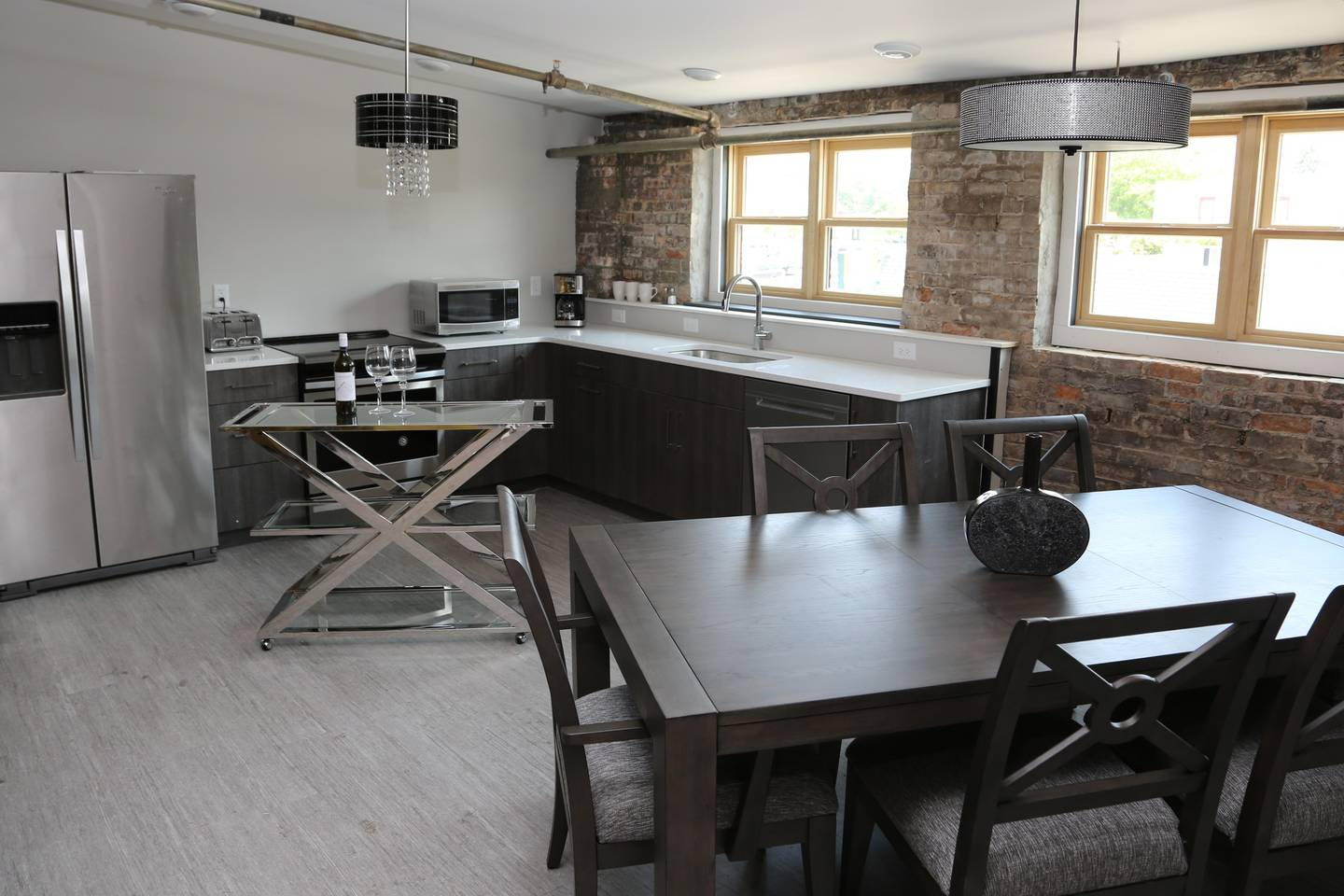 Unit 1 - This two-bedroom, two-full bathroom loft features a more contemporary design and will sleep eight. The master bedroom includes a luxurious king bed, reading area and television. A full kitchen, including stainless appliances, dishes and other kitchenware also includes an island and a dining table to seat eight. Exposed brick, contemporary furnishings and interesting architectural details make the great room a wonderful place for family and friends to gather.