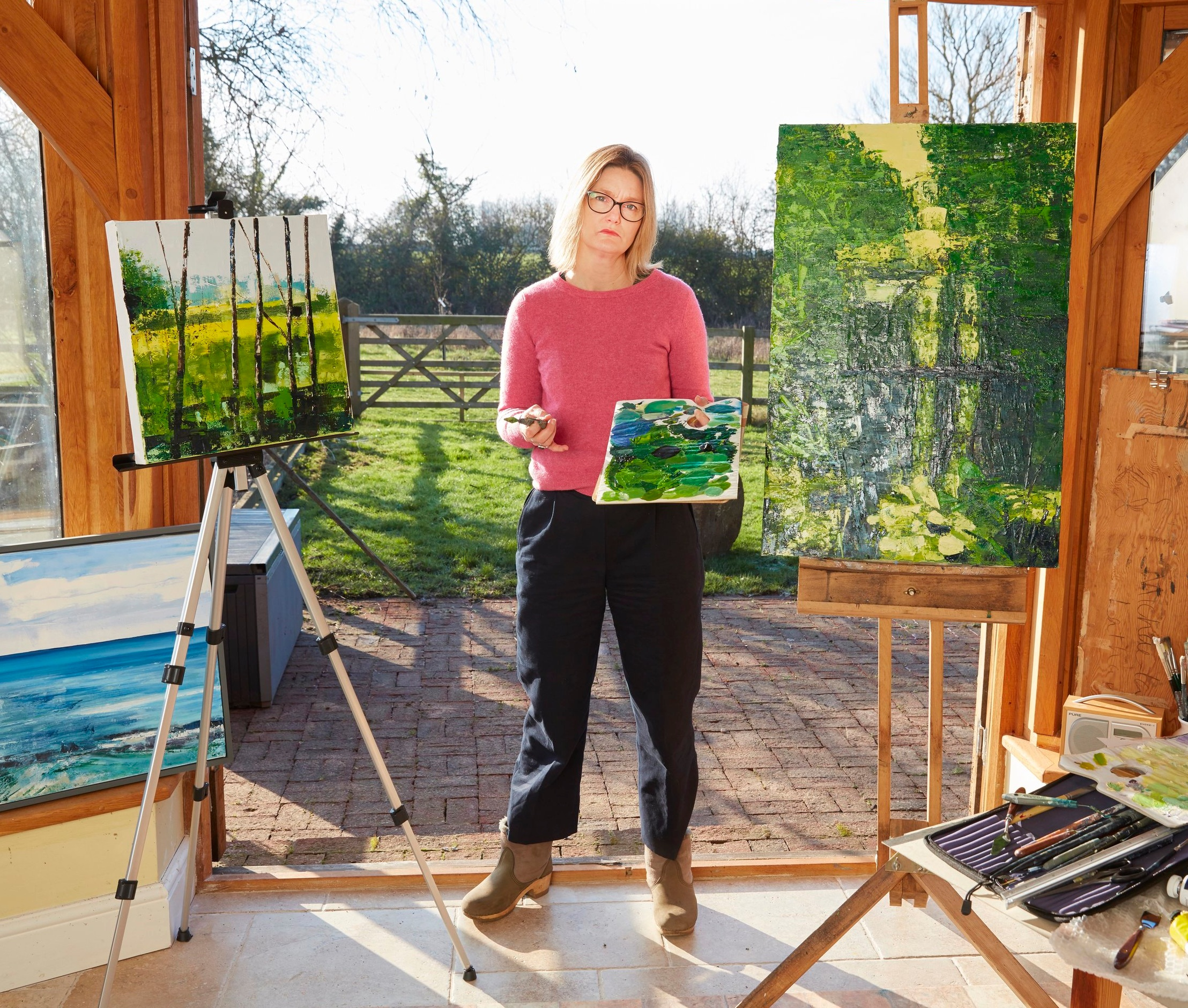 Artist Michaela in her studio. Behind the gate and fence outside is the field where EDF propose locating a construction compound and the start of the major road to Sizewell.