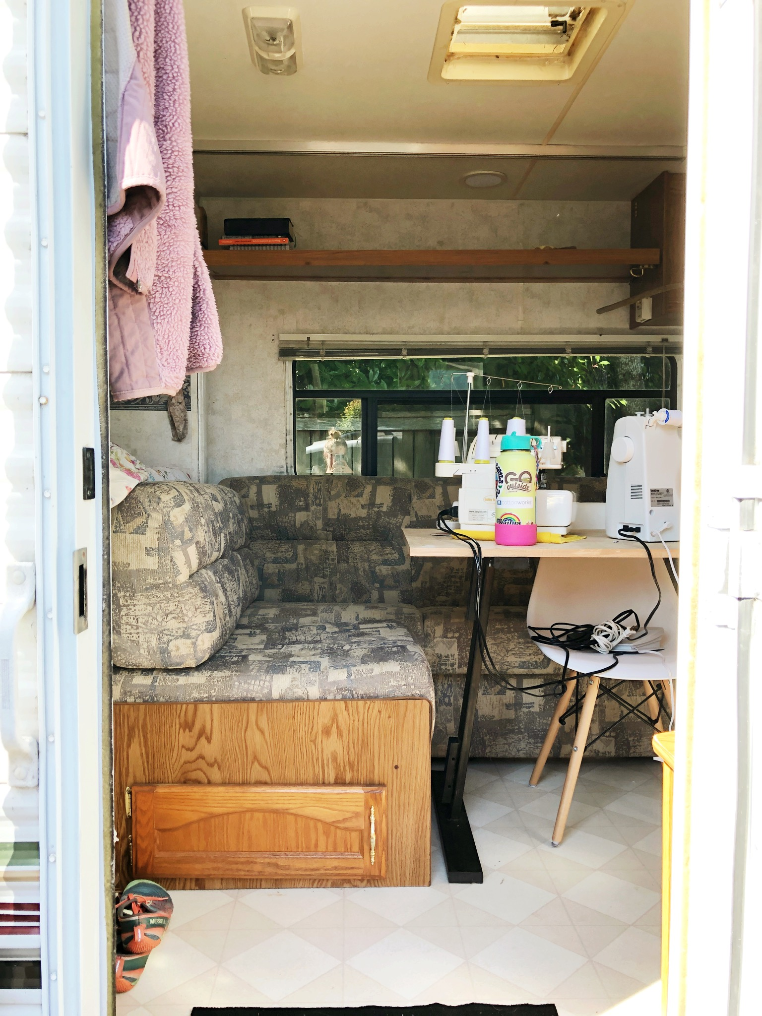This is the entrance. To the left is the bed and to the right is the kitchen and bunk beds. My shoes go to the left (I only have three pairs) and the cords to my sewing machine are put up at night in the chair.
