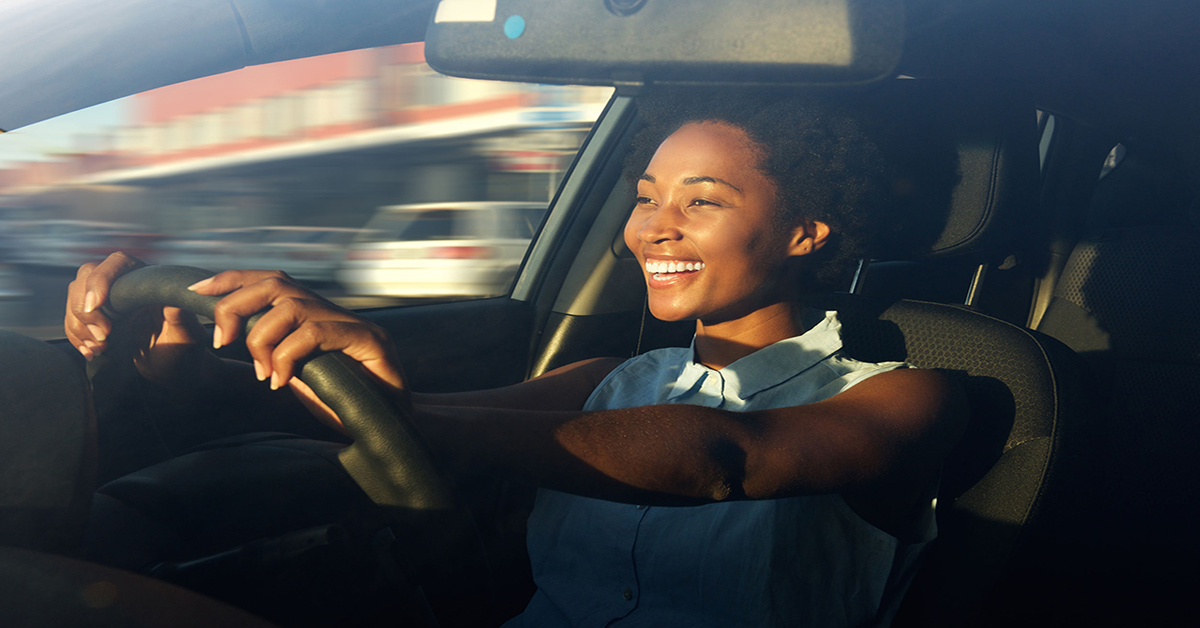 60626289 - portrait of smiling young african american woman driving a car