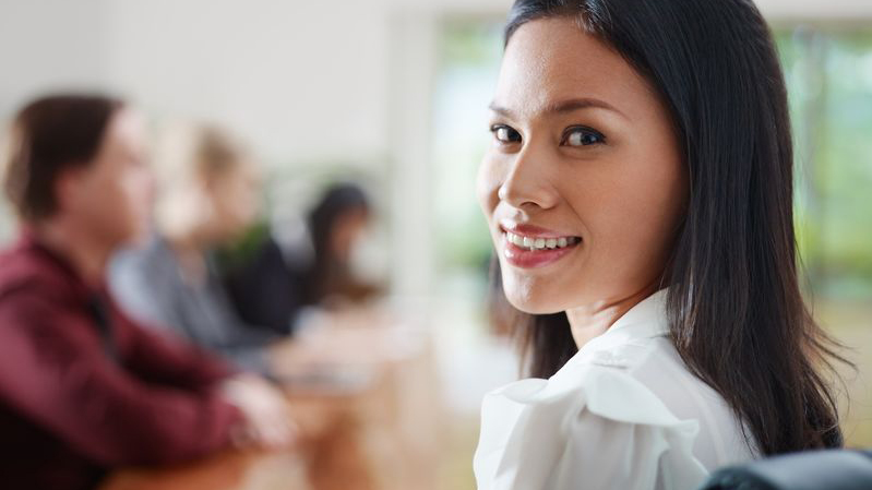 11835796 - attractive young asian business woman smiling and looking over shoulders at business meeting with co-workers.