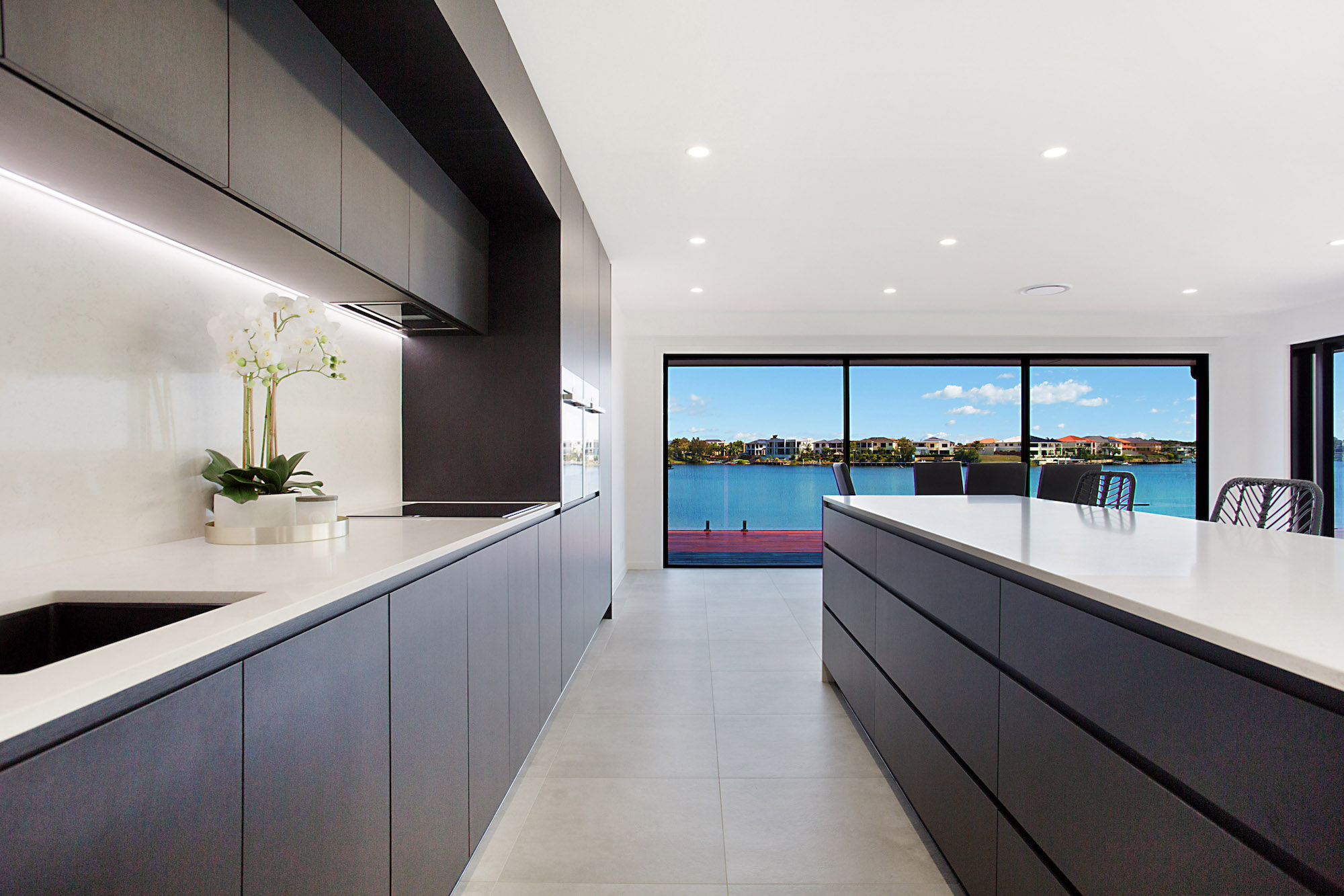 modern black kitchen with marble splash back and LED strip lighting