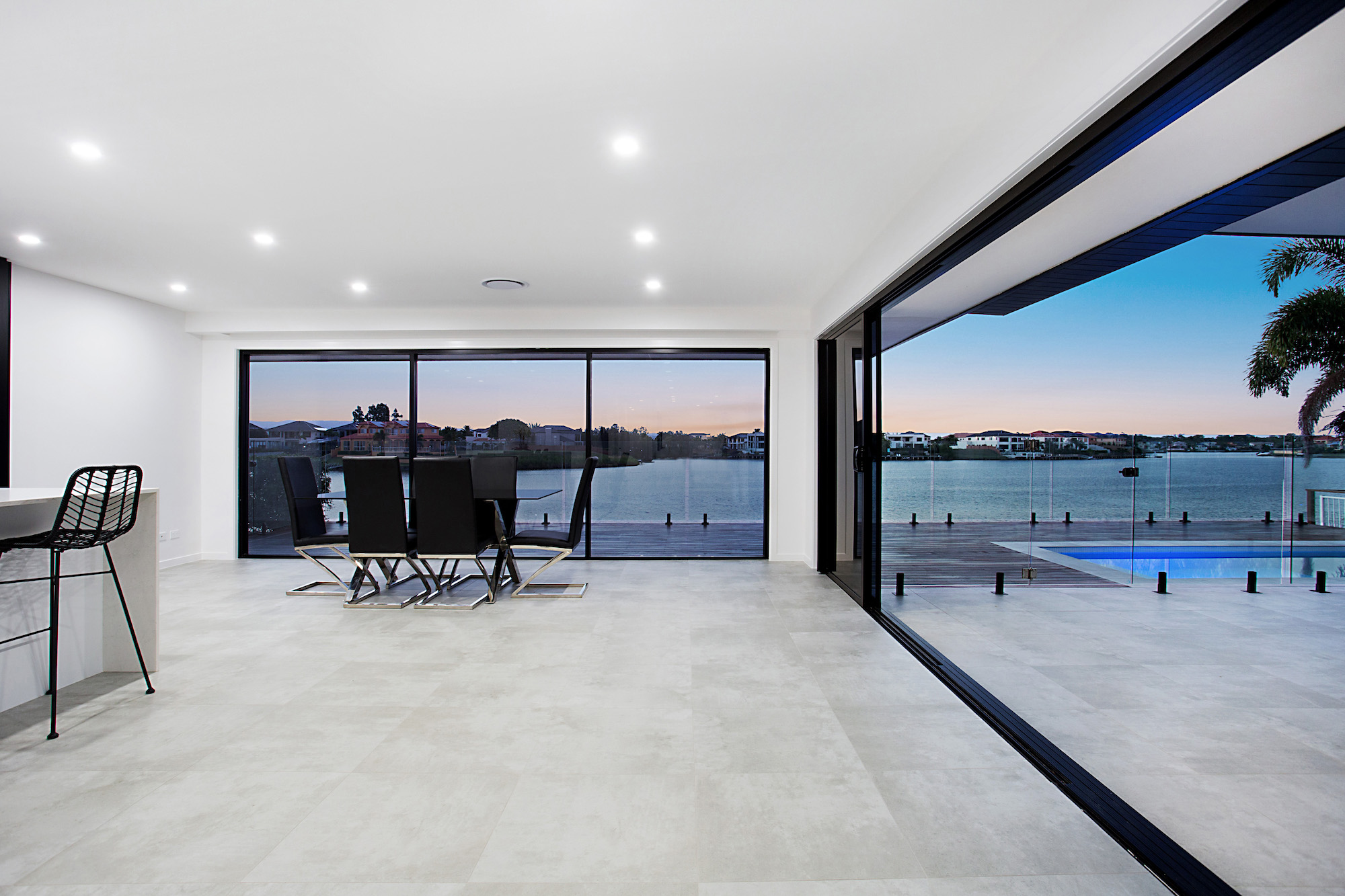 Black stacker doors blend the spaces to create indoor outdoor living with the flowing concrete tiles