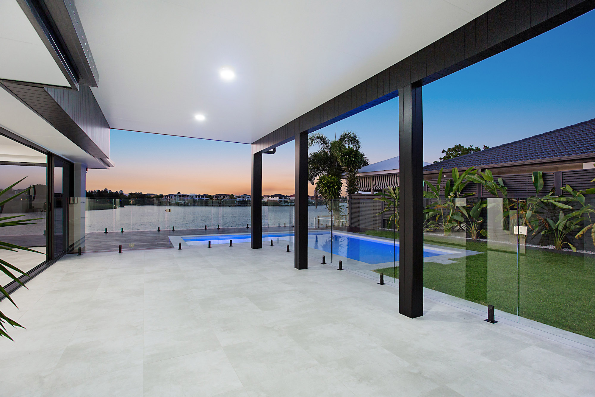 Outdoor patio area with concrete tiles and black cladding