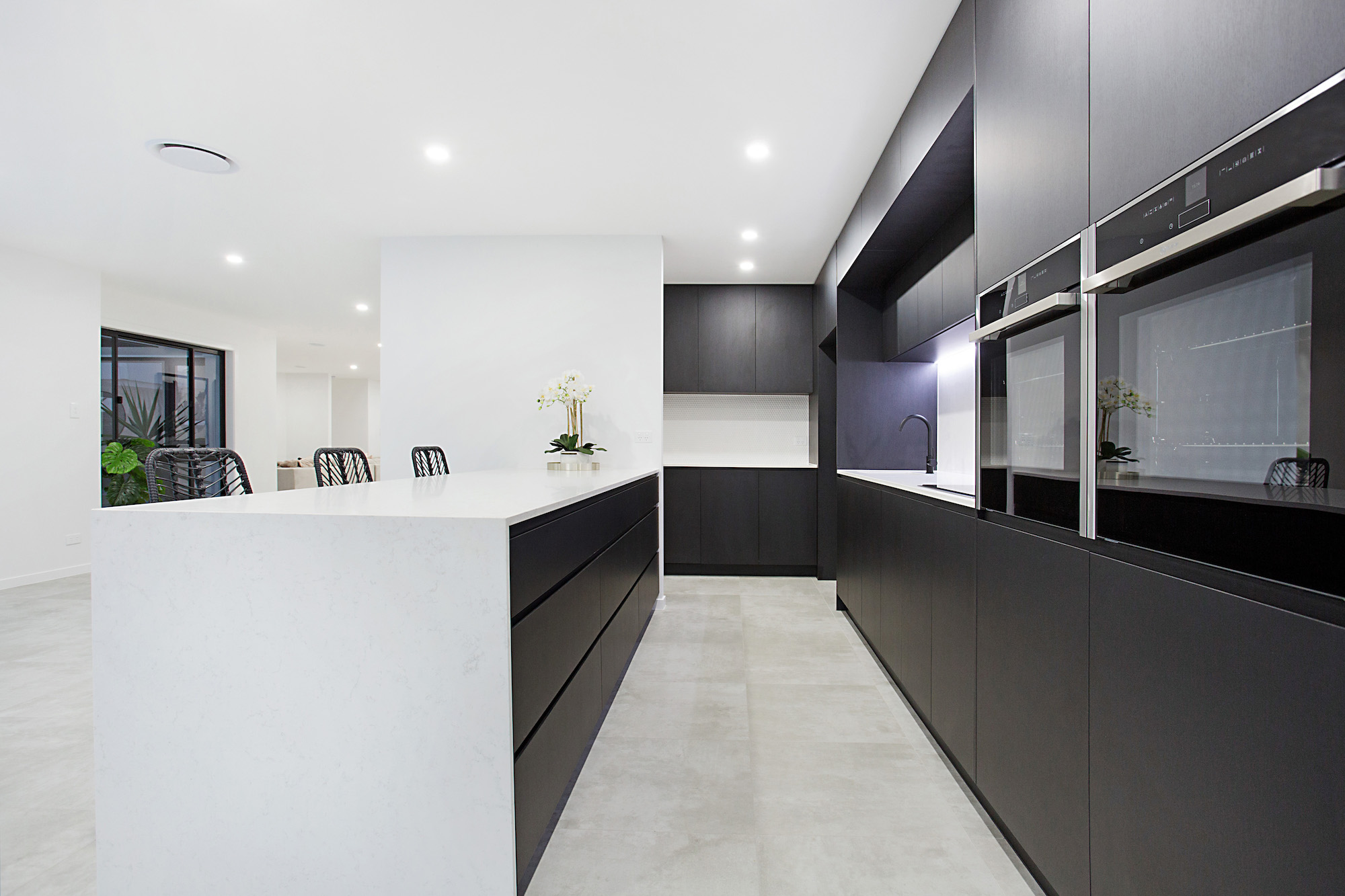 Luxury black and white kitchen with butlers pantry boasting white penny round tiles